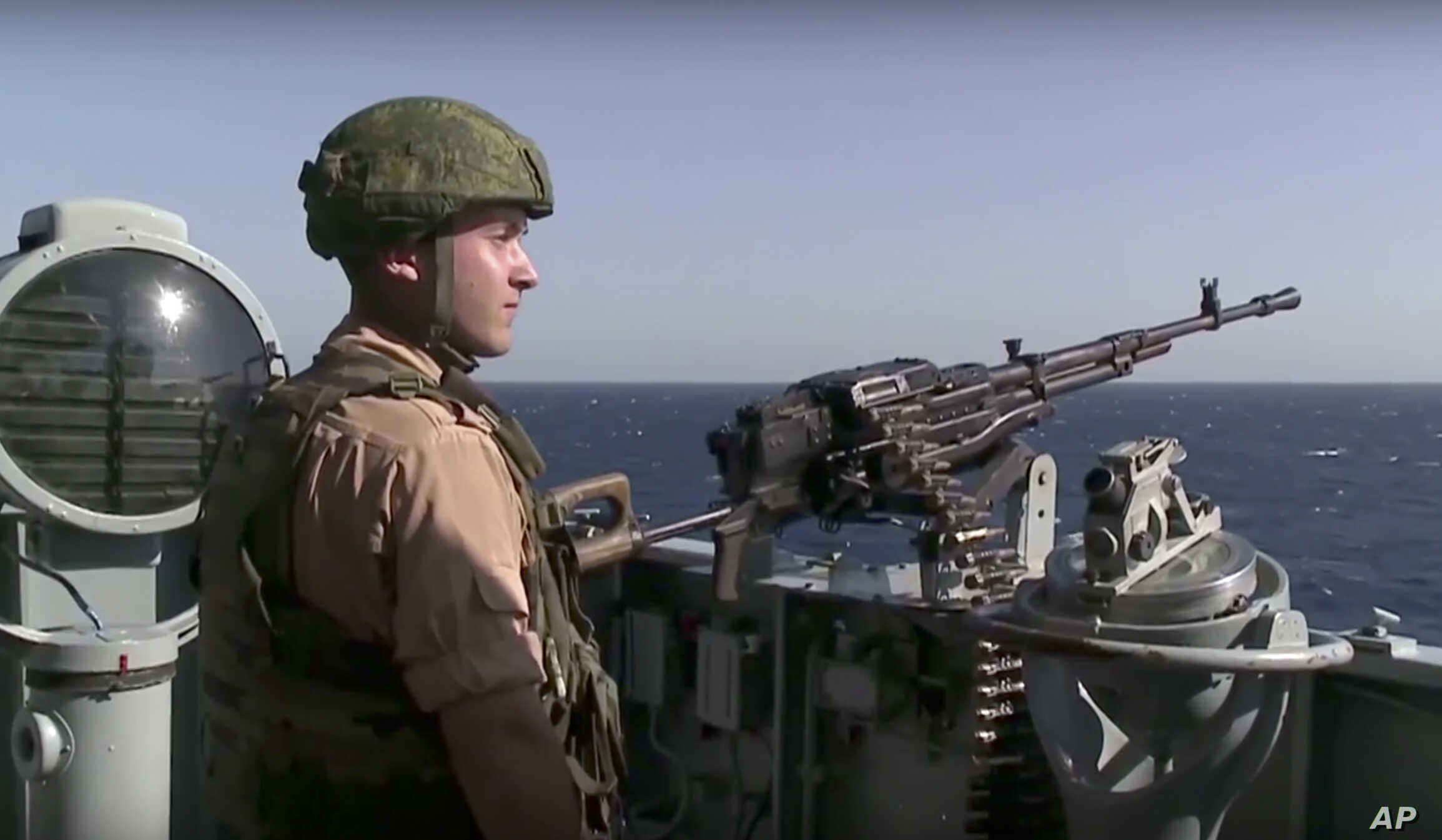 A Russian seaman stands next to a machine gun on the Russian missile cruiser Moskva, near the shore of Syria's province of Latakia, Syria, Nov. 27, 2015.