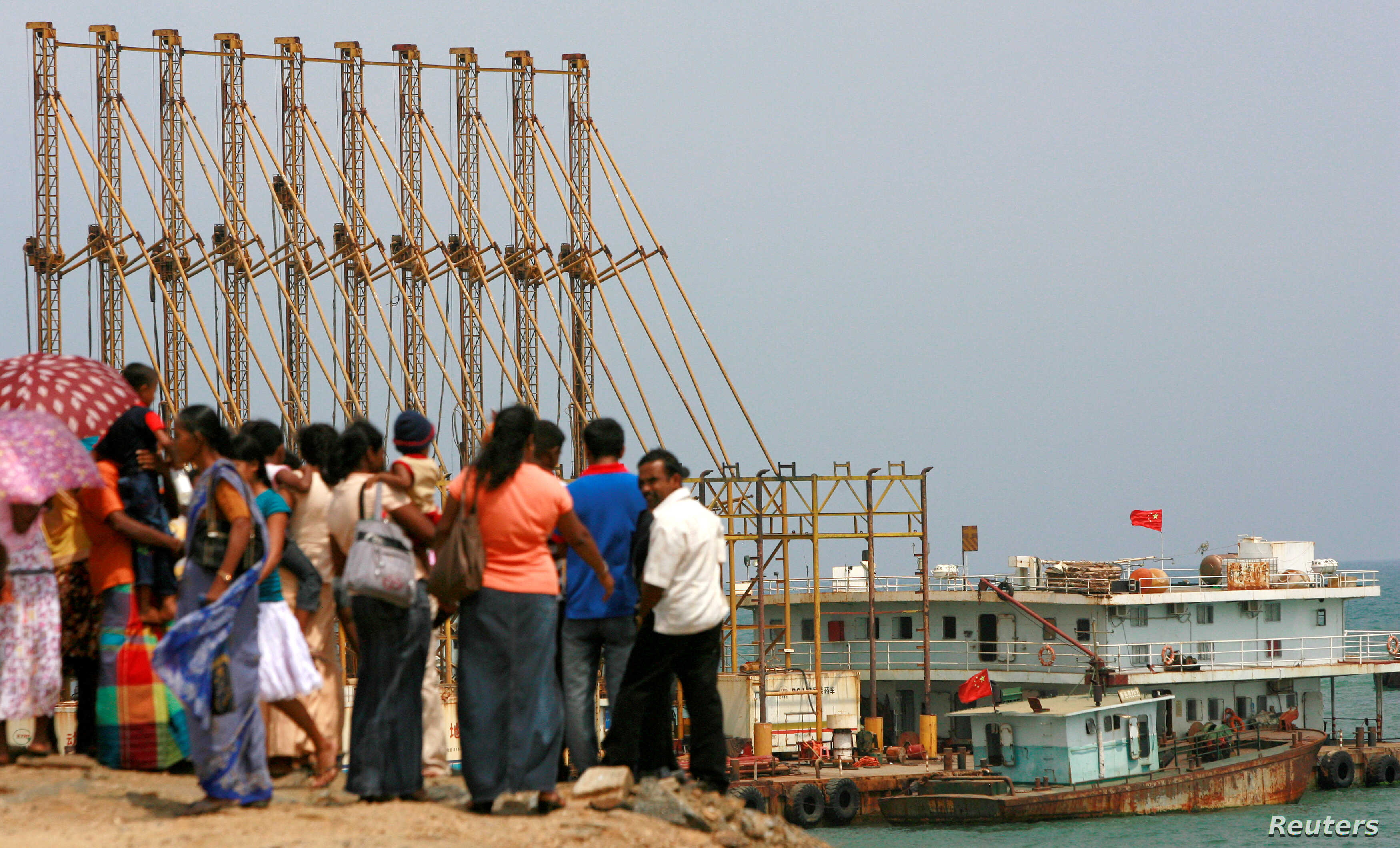 A group of Sri Lankan visitors at the new deep water shipping port watch a Chinese dredging ships work in Hambantota, March 24, 2010.
