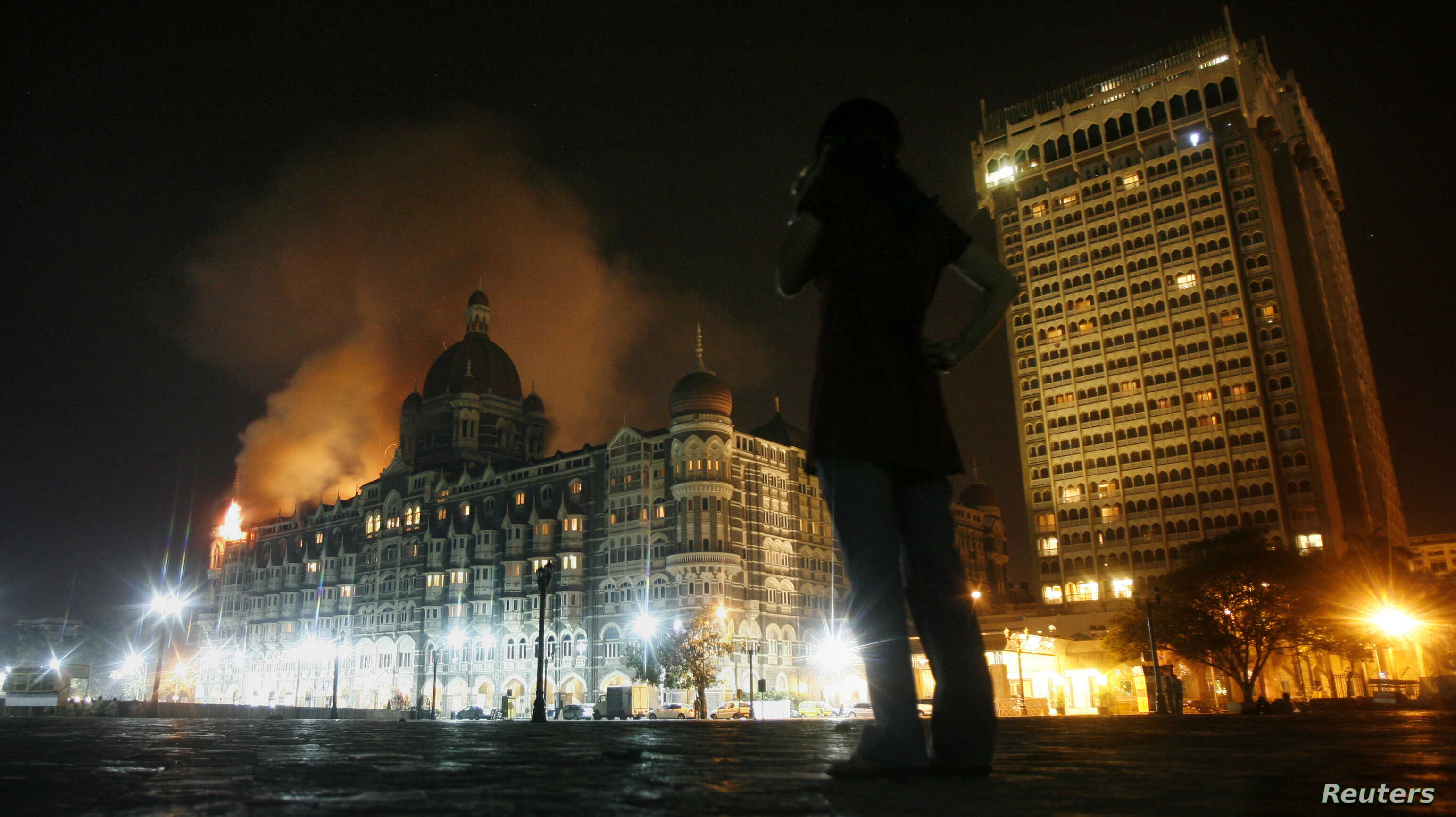 FILE - A reporter talks on her phone as smoke is seen coming from Taj Hotel in Mumbai, November 27, 2008, where terrorists were holding hostages during an attack that began the previous day.