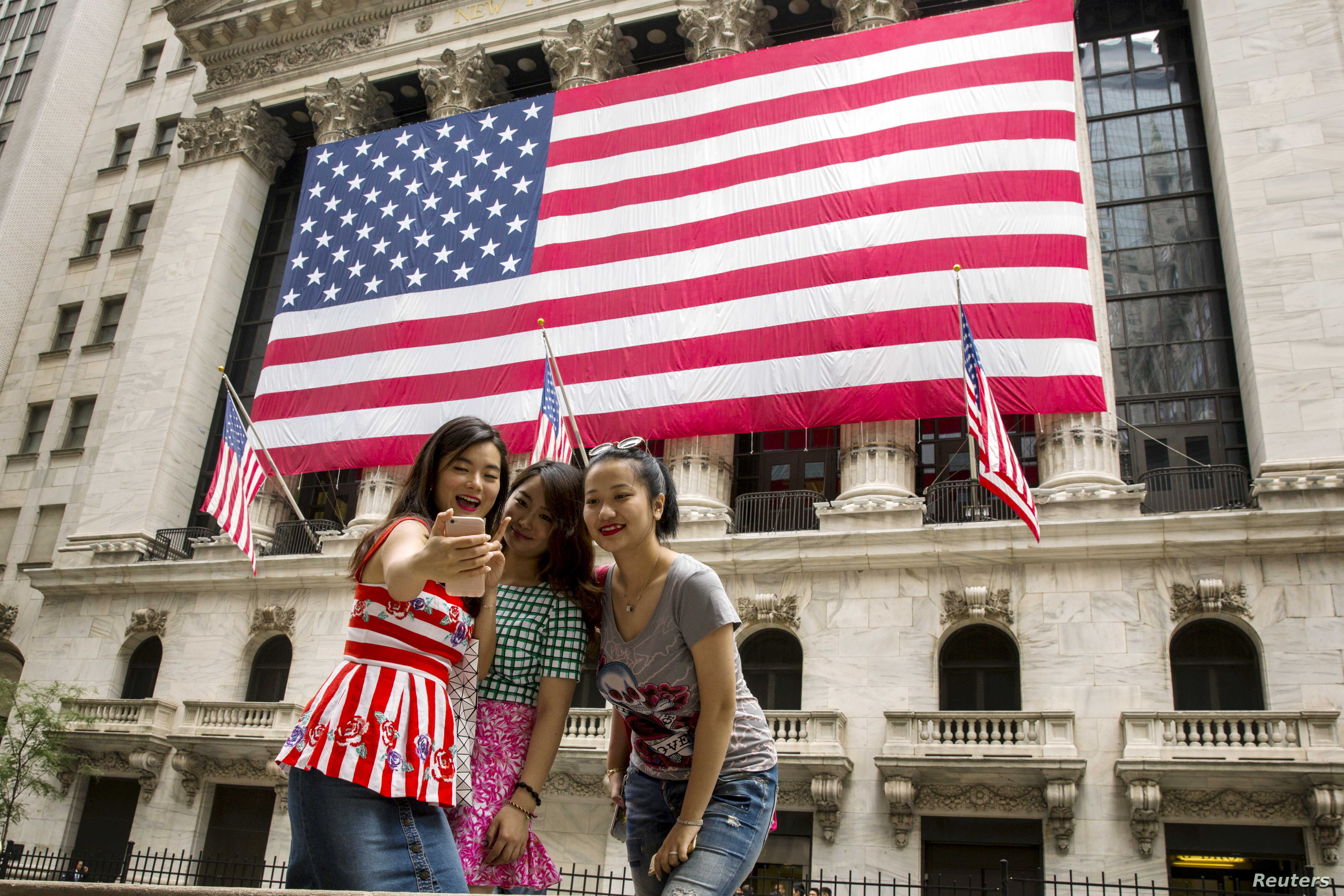 FILE - Chinese tourists take a selfie outside of the New York Stock Exchange, in New York, July 8, 2015.