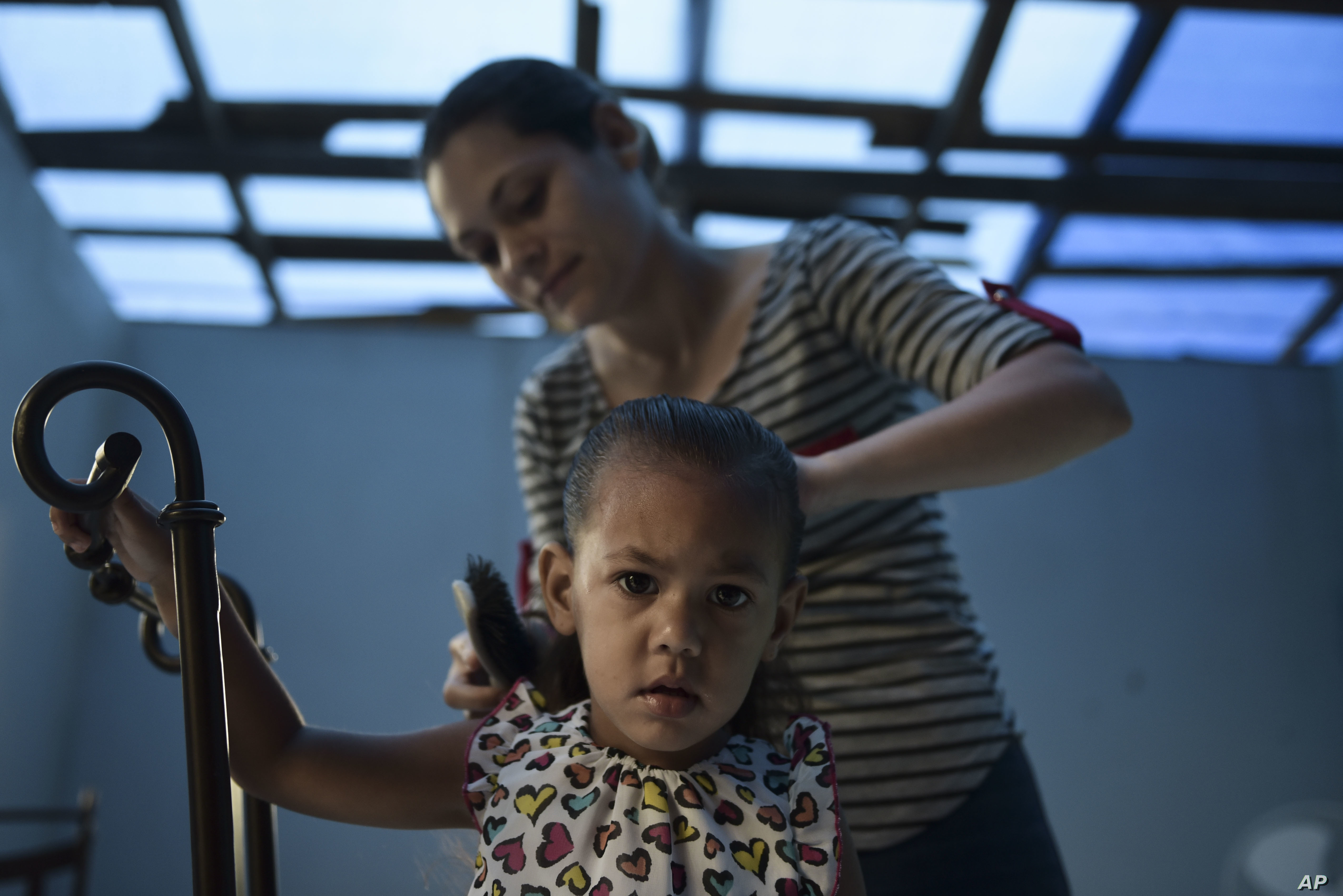 Wilmarie Gonzalez Rivera combs the hair of her 2-year-old daughter, Yeinelis Oliveras Gonzalez, in Morovis, Puerto Rico, Dec. 22, 2017. The roof of their home is now a blue tarp and some recycled zinc pieces, after the passage of Hurricane Maria.