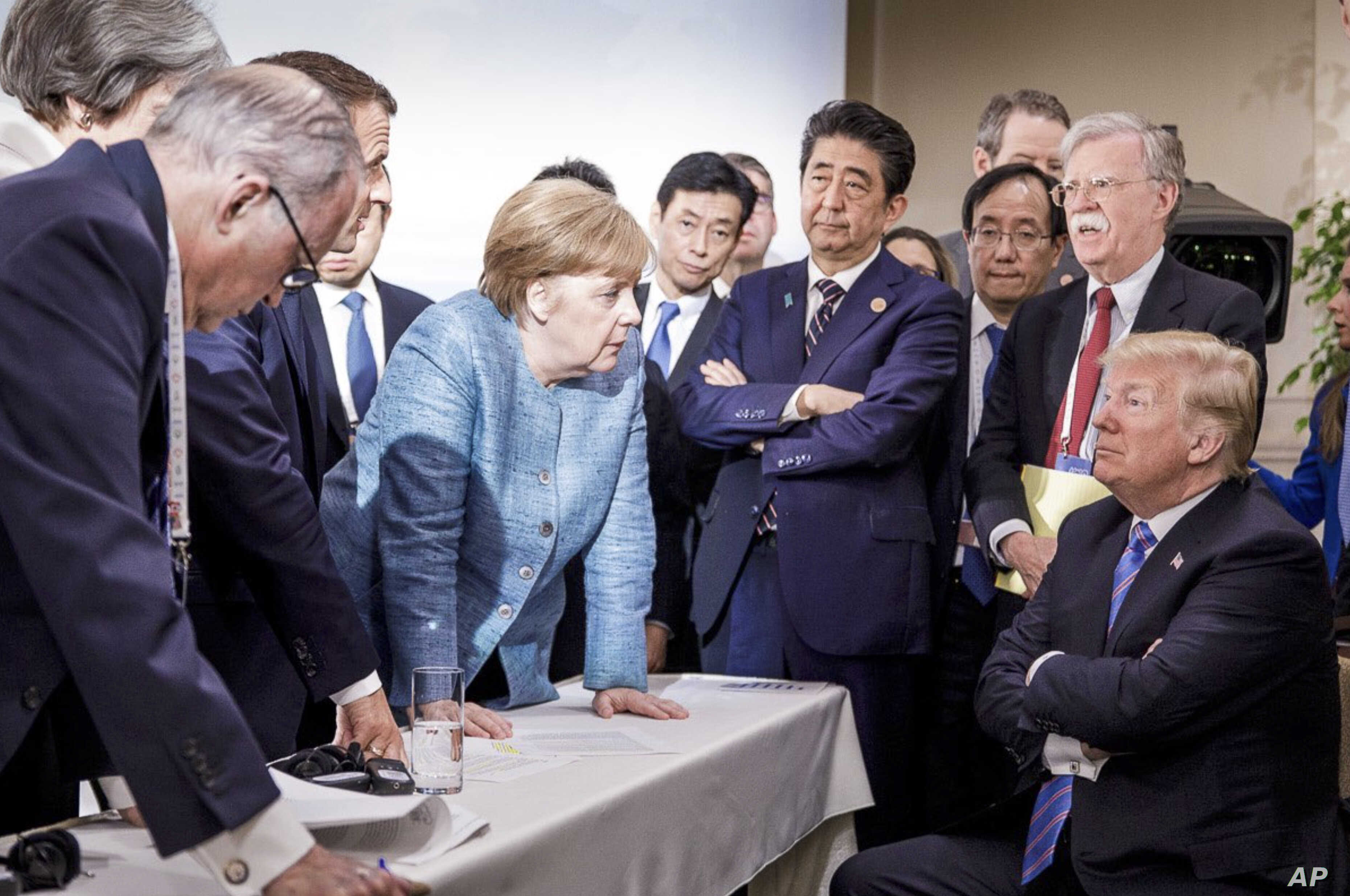 In this photo made available by the German Federal Government, German Chancellor Angela Merkel, center, speaks with U.S. President Donald Trump, seated at right, during the G7 Leaders Summit in La Malbaie, Quebec, Canada, on June 9, 2018.