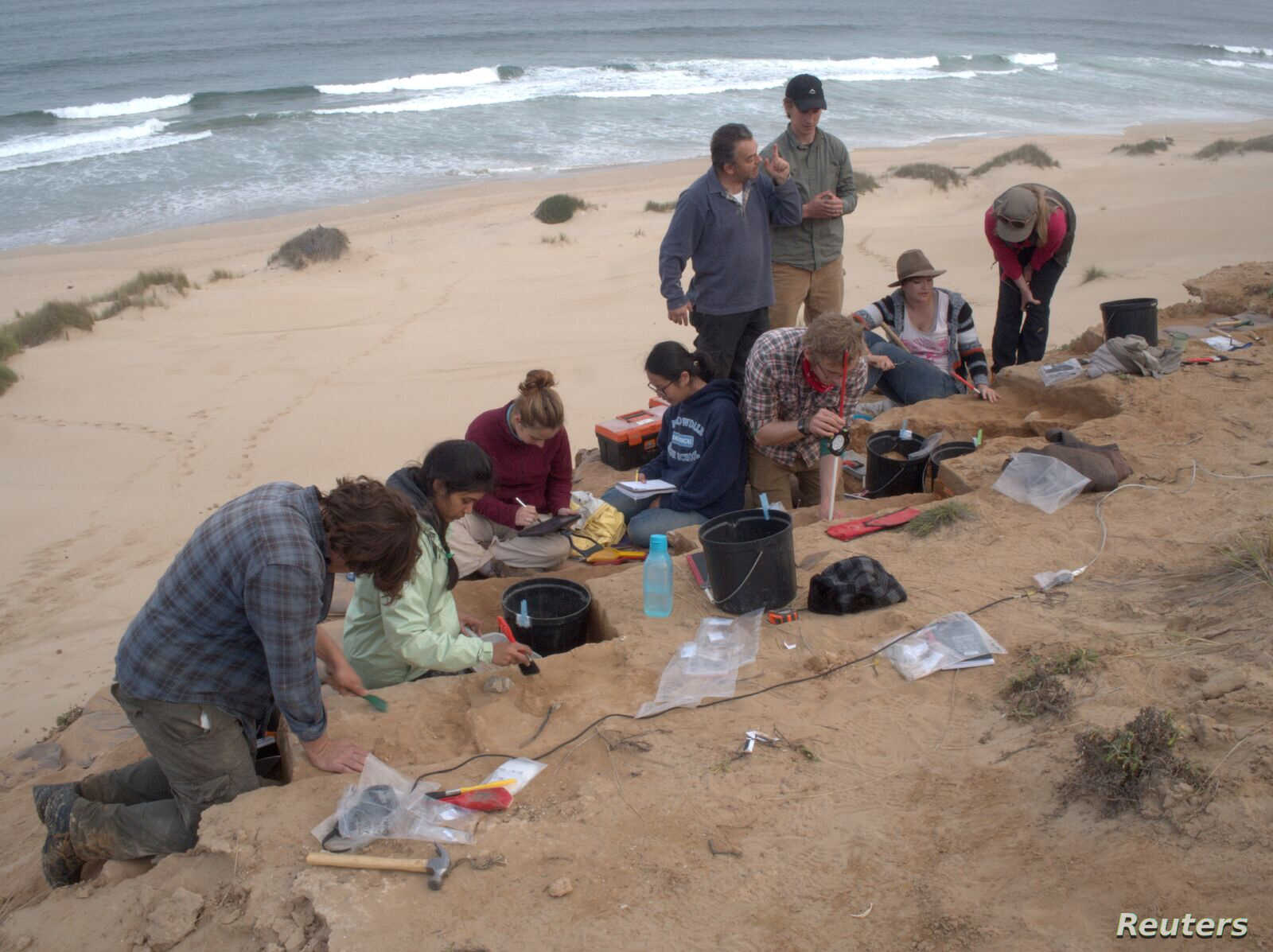 Members of a research team are pictured conducting excavations at the Vleesbaai archeological site on the south coast of South Africa where humans made stone tools about 74,000 years ago in this 2016 photo released March 12, 2018.