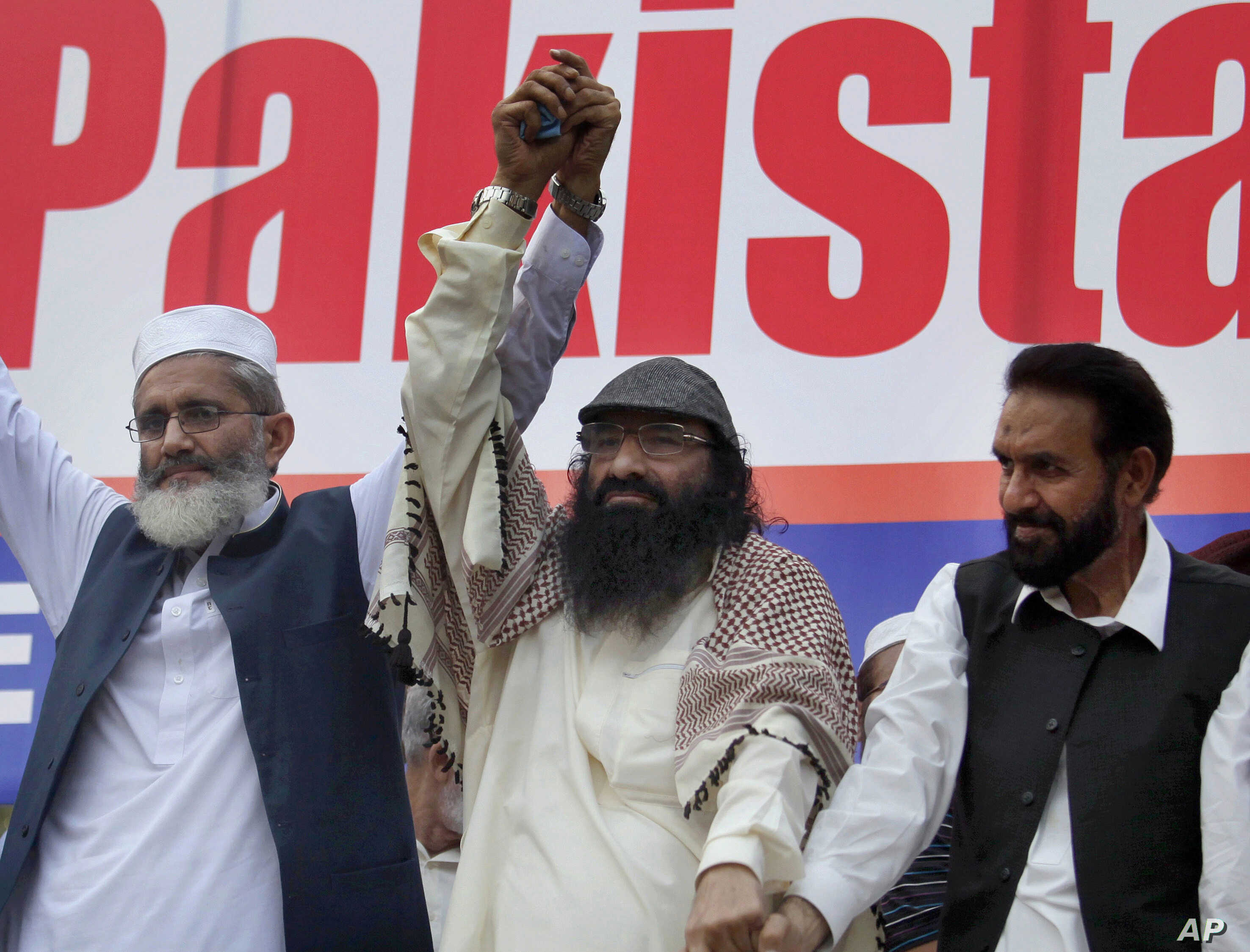 FILE - Leader of Hizbul Mujahideen, Syed Salahuddin, center, joins hands with leaders of Jamaat-e-Islami, Sirajul Haq, left, and Mian Aslam, during an anti-India rally in Islamabad, Pakistan, July 24, 2016.