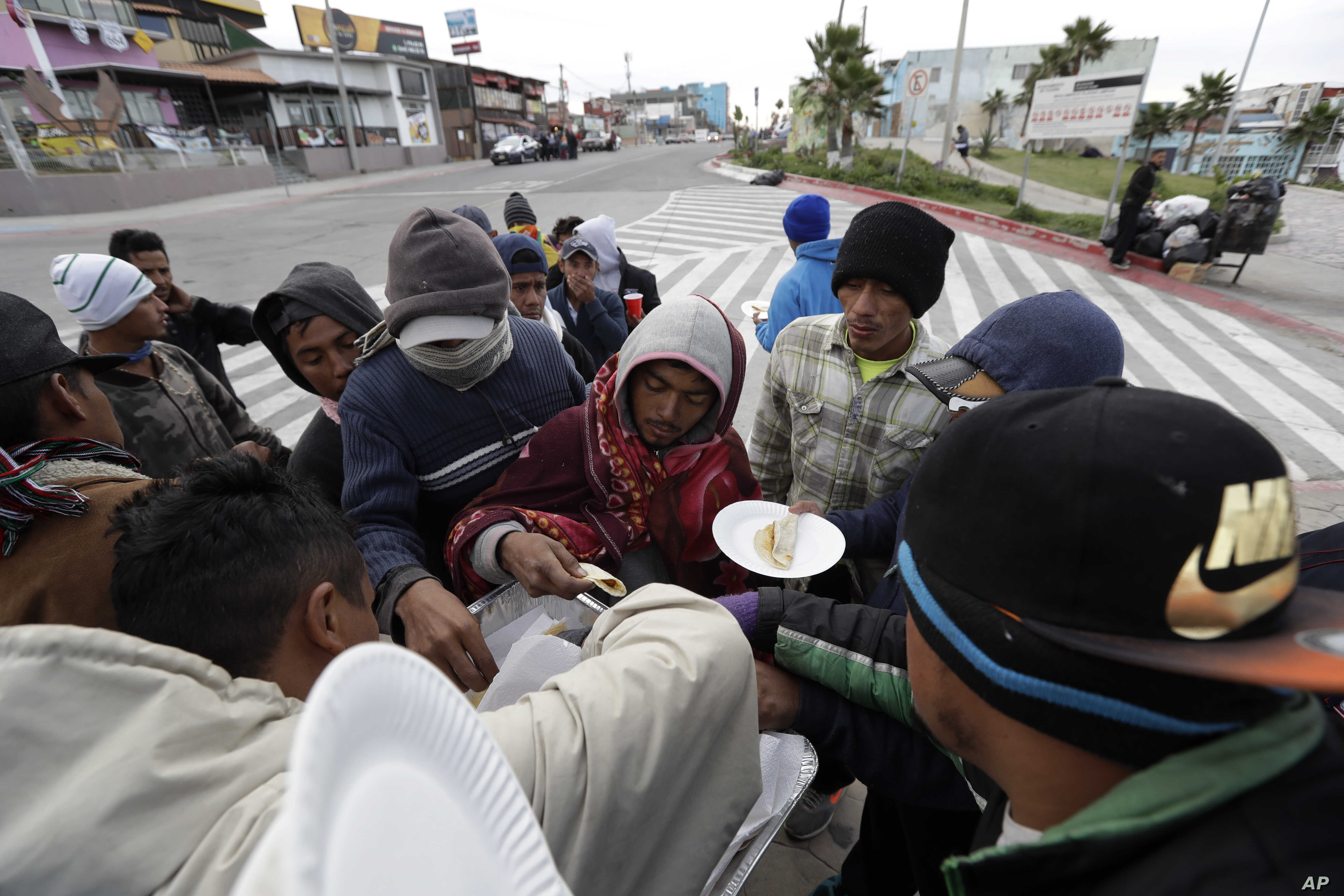 A volunteer hands out tacos to a group of migrants from Central America in Tijuana, Mexico, Nov. 14, 2018.