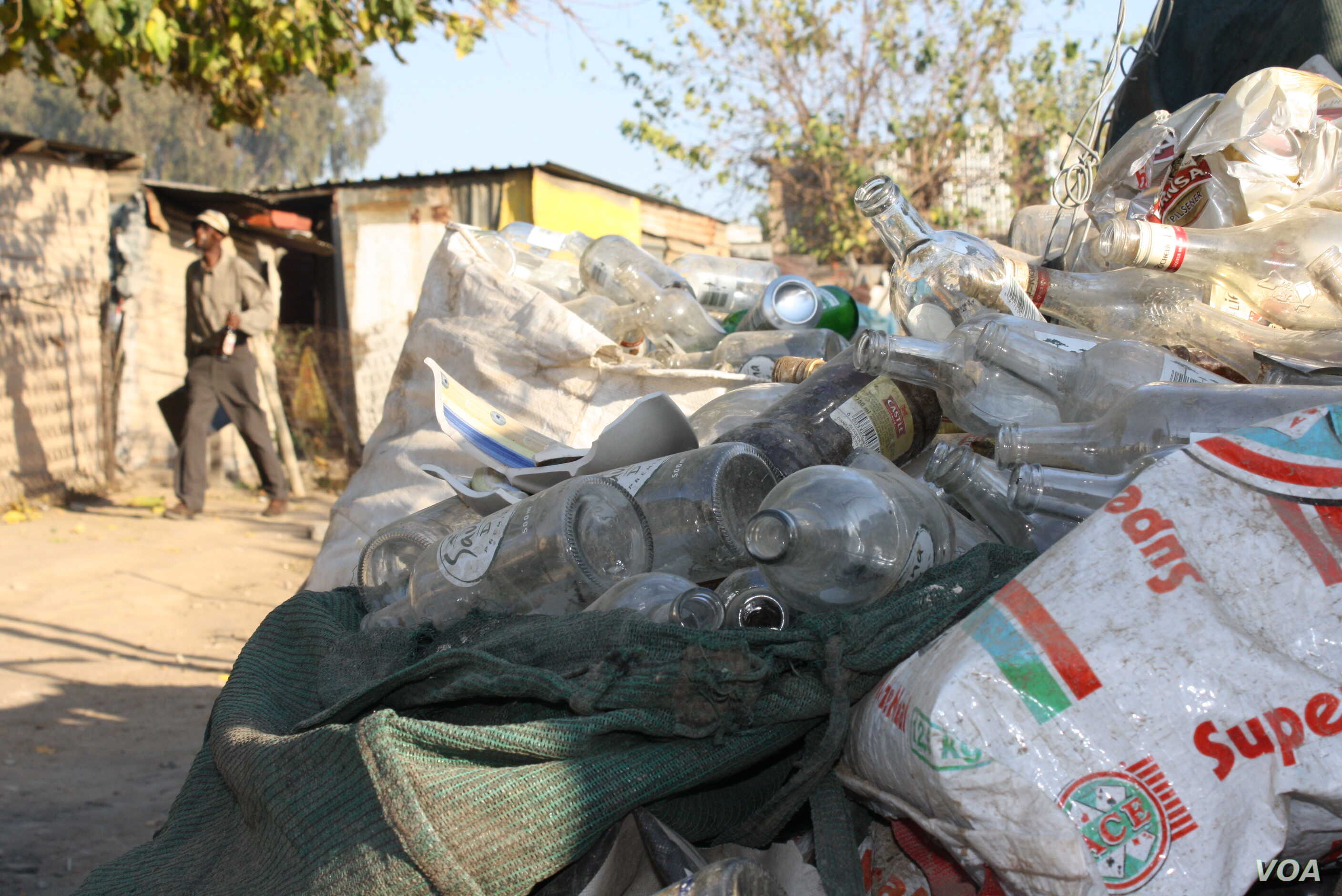 Piles of empty liquor bottles are everywhere in the streets of Diepsloot. (D. Taylor/VOA)
