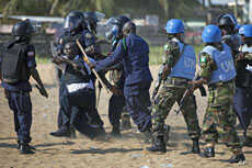 Liberian riot policeman drag away a commander who fired live rounds while storming the compound of the opposition Congress for Democratic Change headquarters in the capital Monrovia, Liberia, November 7, 2011.