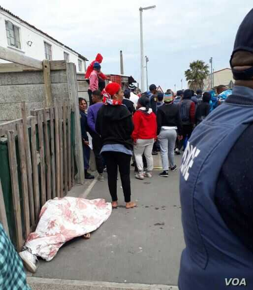 People gather near the covered body of a teenager killed in a gang shootout in Hanover Park, a township of Cape Town, South Africa, Sept. 19, 2017. A police officer stands in the foreground. (Special to VOA)
