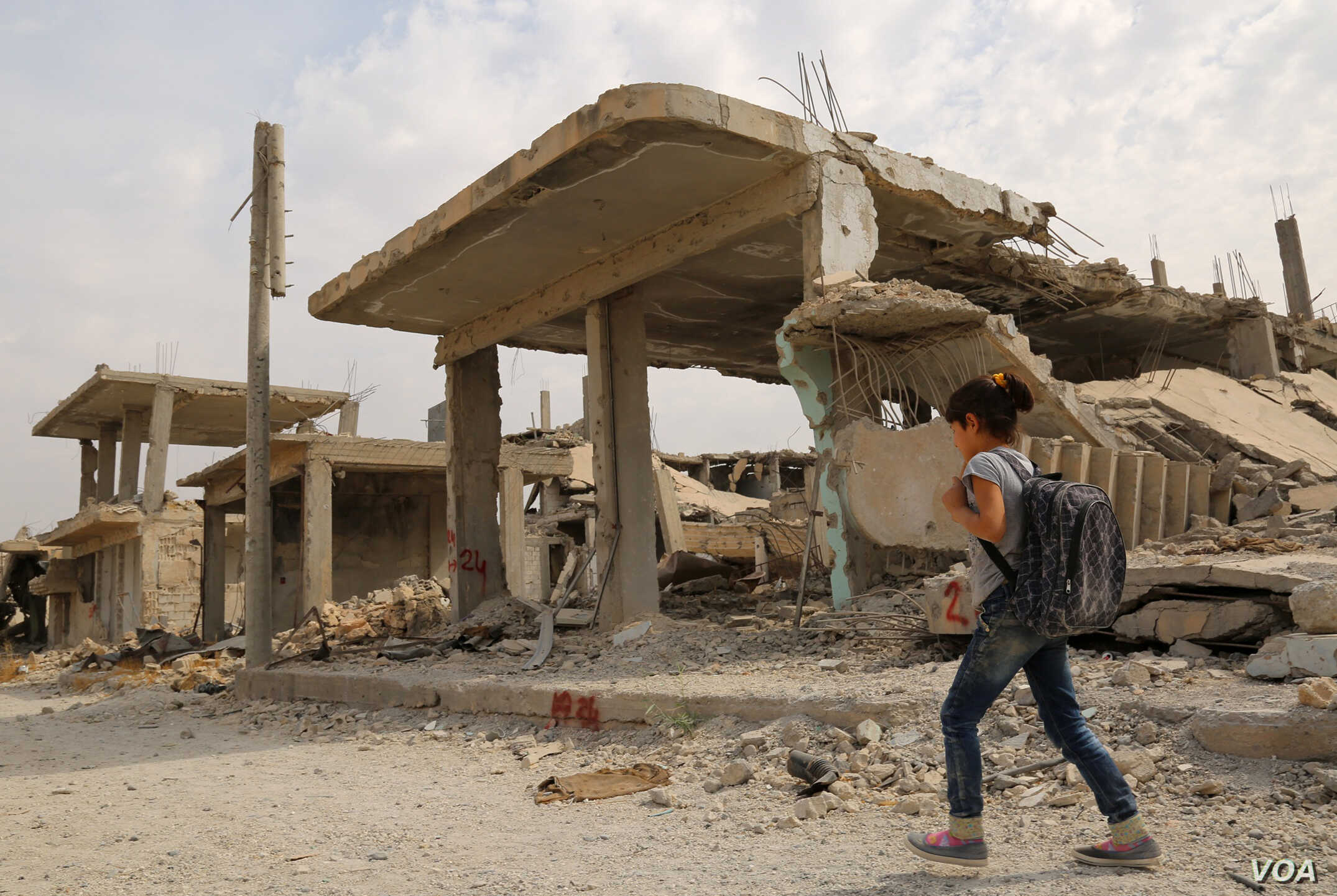 Syrian children walk past debris while heading to school on the second day of the new school year on Oct. 6, 2015 in the Syrian Kurdish town of Kobani.