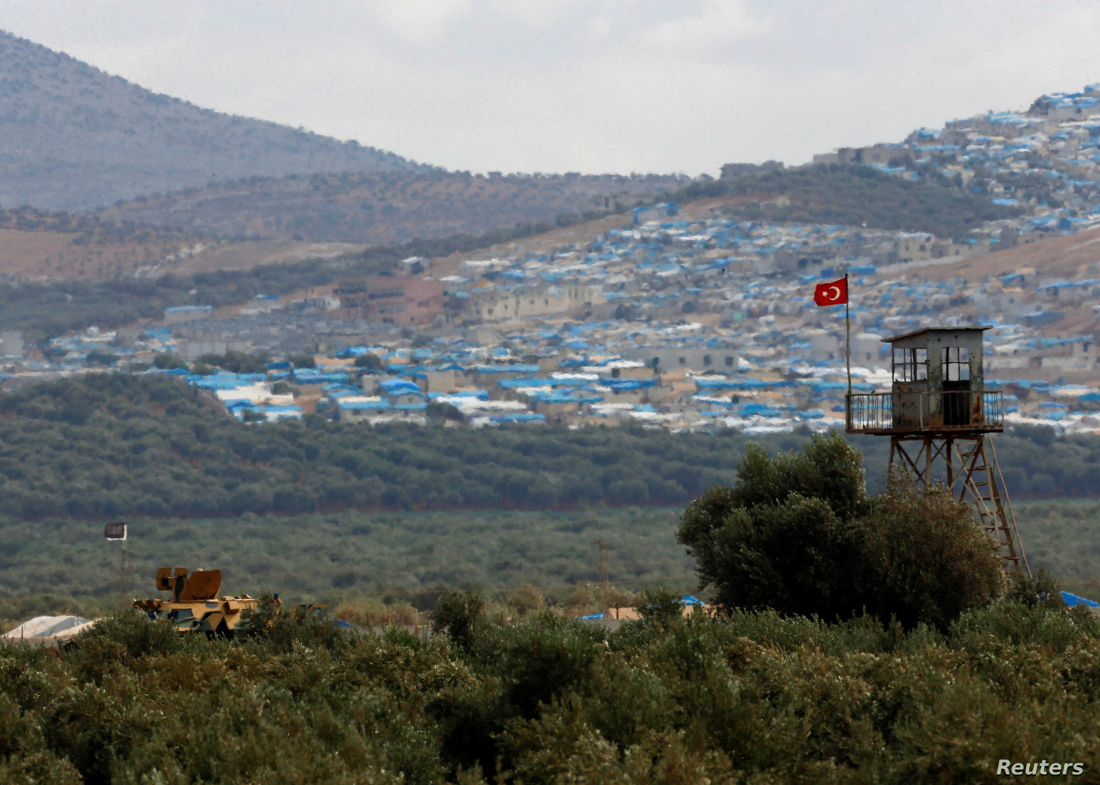 A Turkish military armored vehicle patrols on the border line located opposite the Syrian town of Atimah, Idlib province, in this picture taken from Reyhanli, Hatay province, Turkey Oct. 10, 2017.