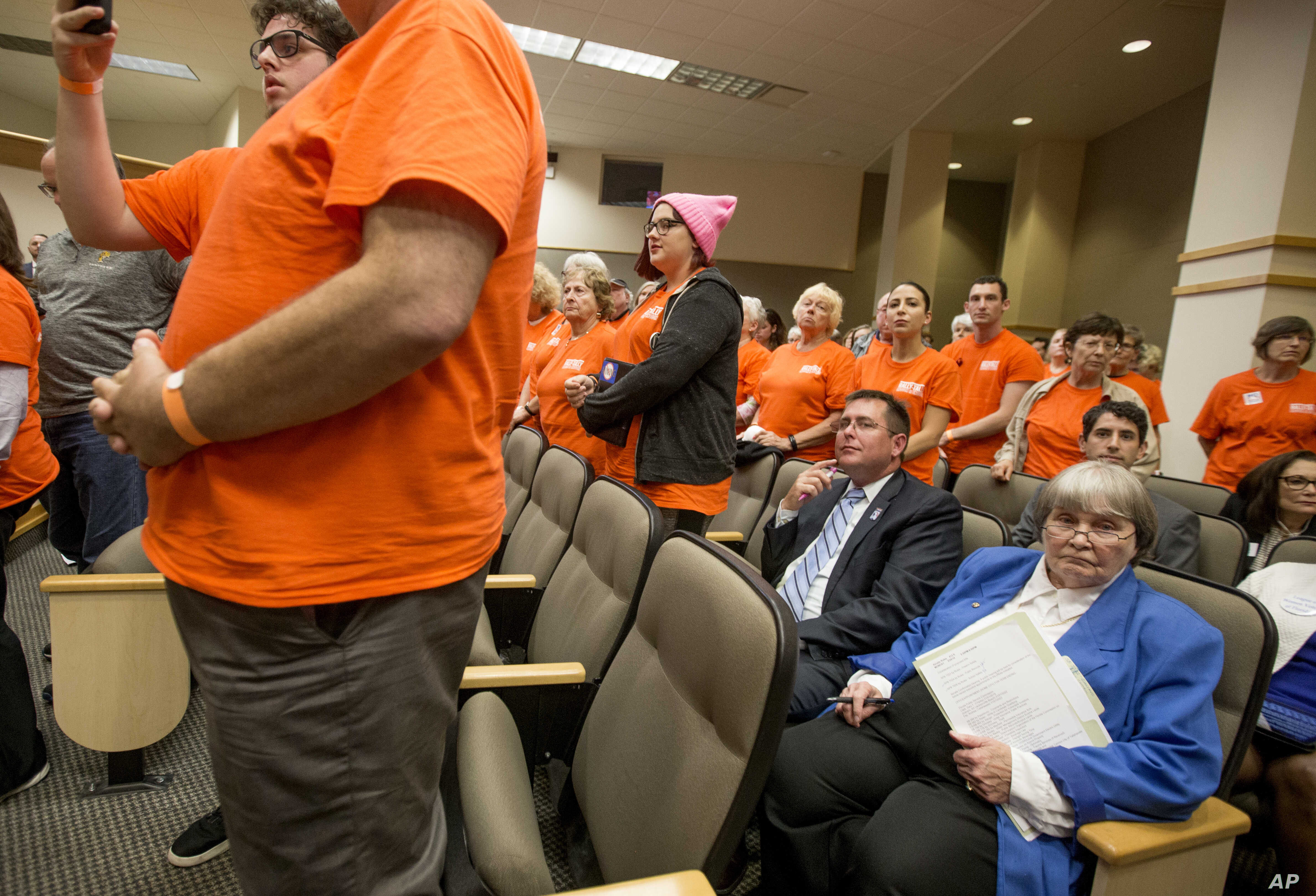 Gun lobbyist Marion Hammer, right, and Eric Friday, general counsel for Florida Carry, sit among protesters during the Senate Rules Committee meeting on gun safety at the Florida state Capitol after a rally in Tallahassee, Fla., Feb. 26, 2018.