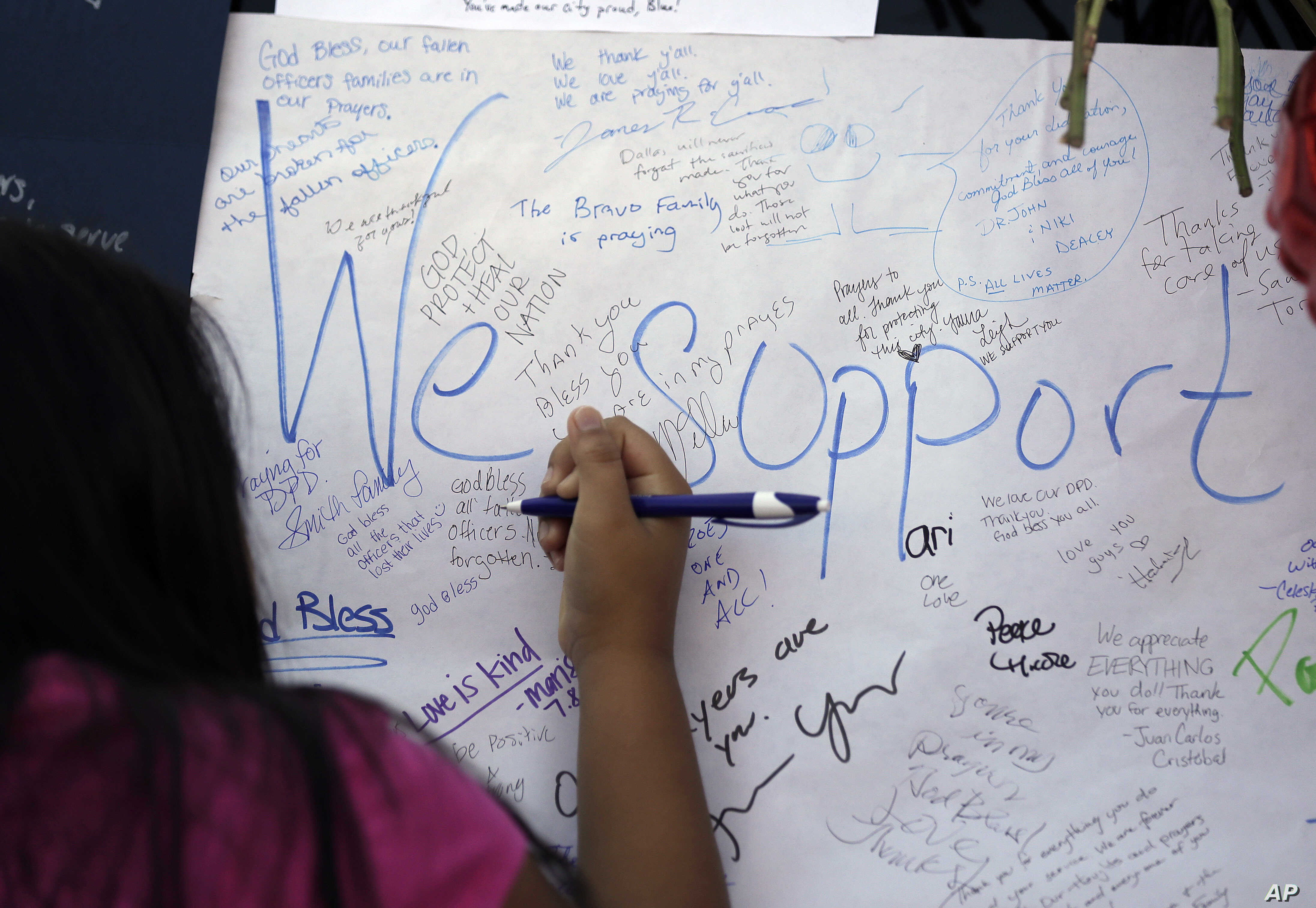 Jasmine Ruiz writes a note at a makeshift memorial in front of the police department in Dallas, July 9, 2016. Five police officers were killed in a shooting in downtown Dallas on Thursday.