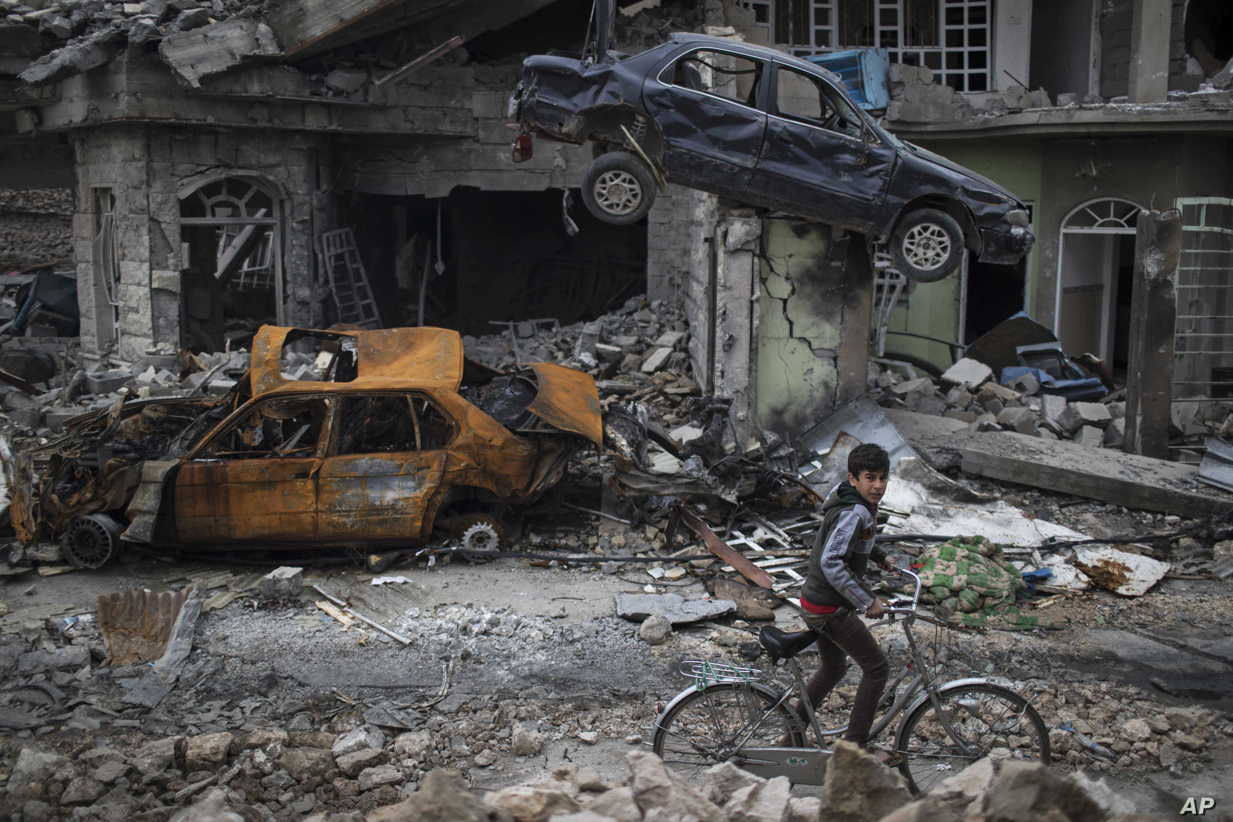 A boy rides his bike past destroyed cars and houses in a neighborhood recently liberated by Iraqi security forces, on the western side of Mosul, Iraq, Sunday, March 19, 2017.