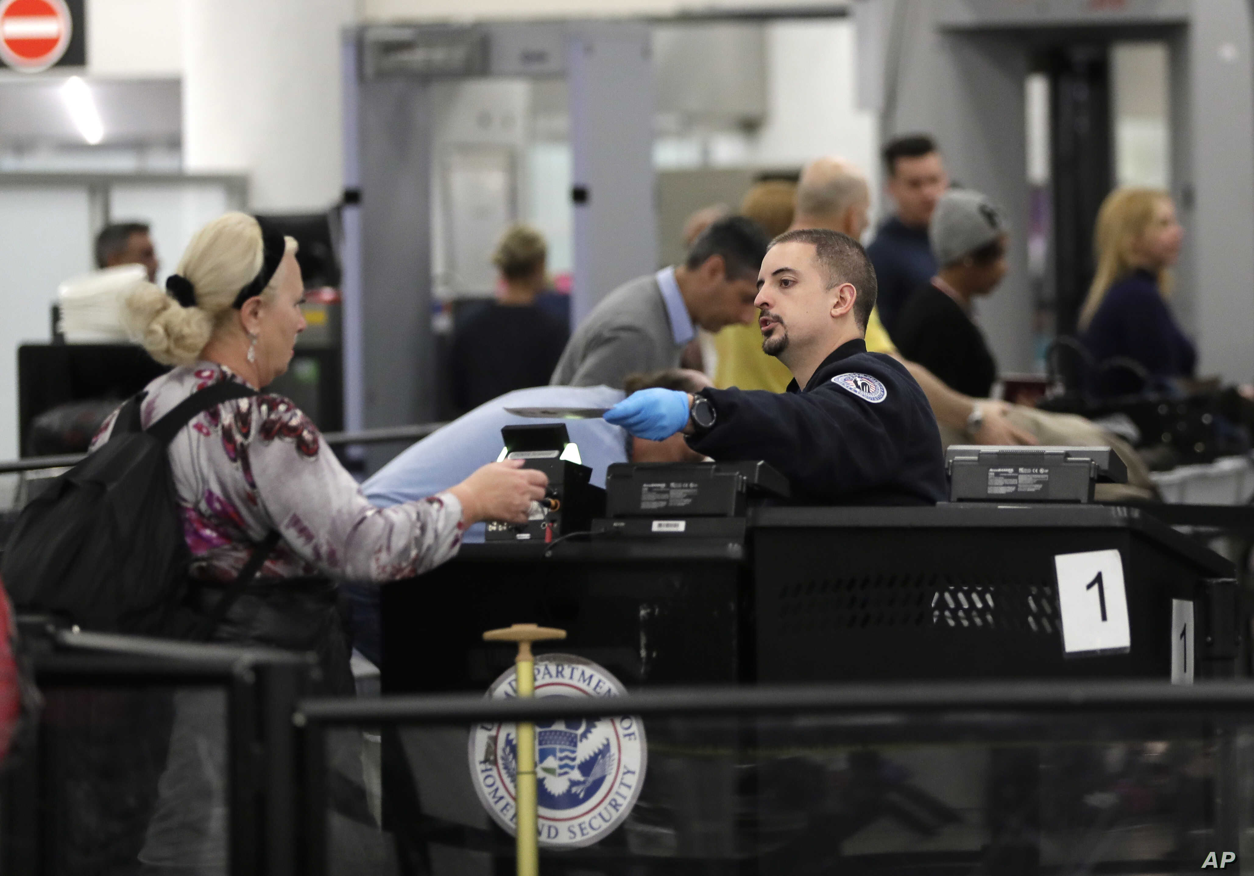 A Transportation Security Administration official works at the entrance to Concourse G at Miami International Airport in Miami, Jan. 11, 2019.