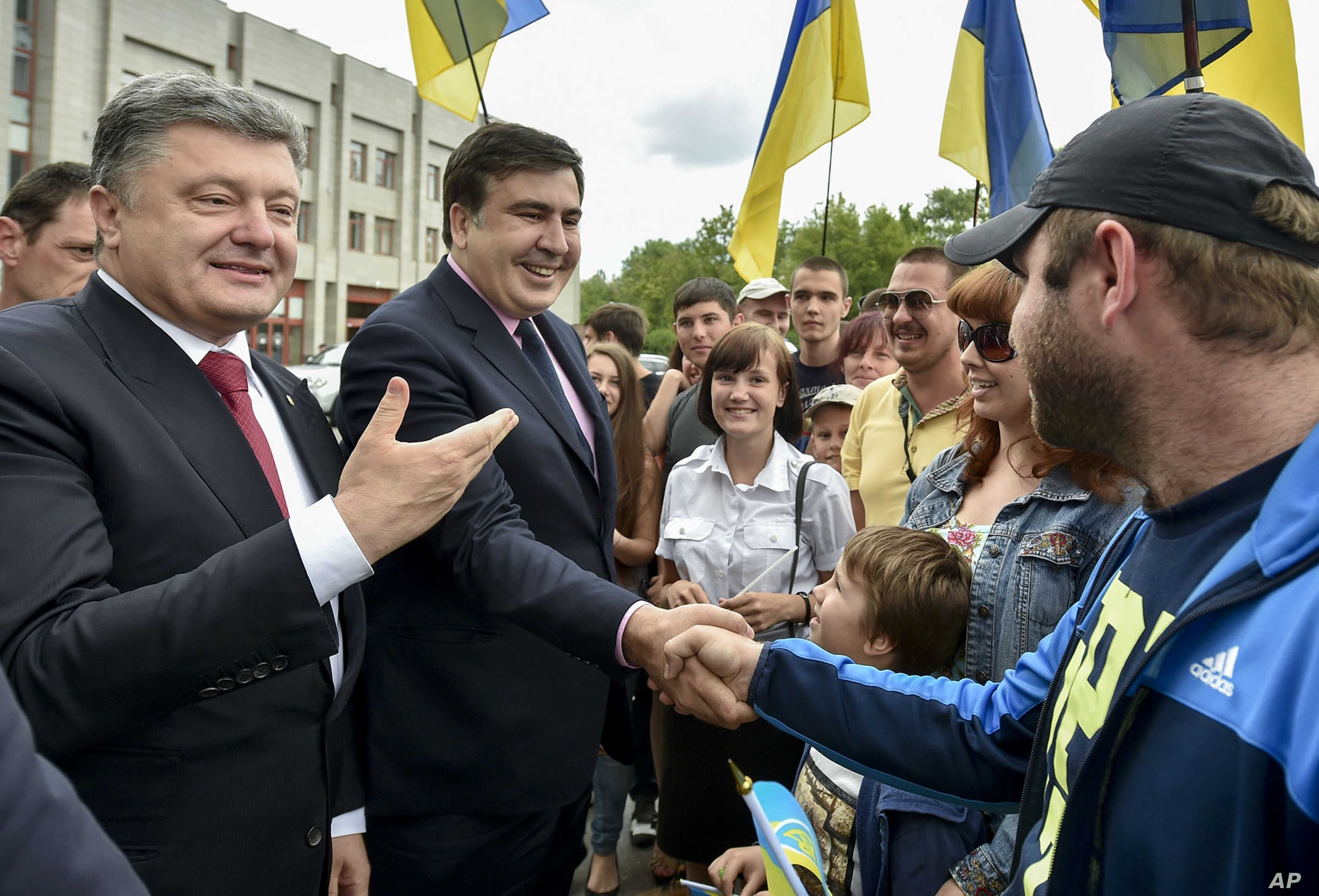 Seen during better times, Ukrainian President Petro Poroshenko, left, and then newly-appointed Odesa region governor Mikheil Saakashvili, second left, shake hands with local residents, in Odesa, Ukraine, May 30, 2015.