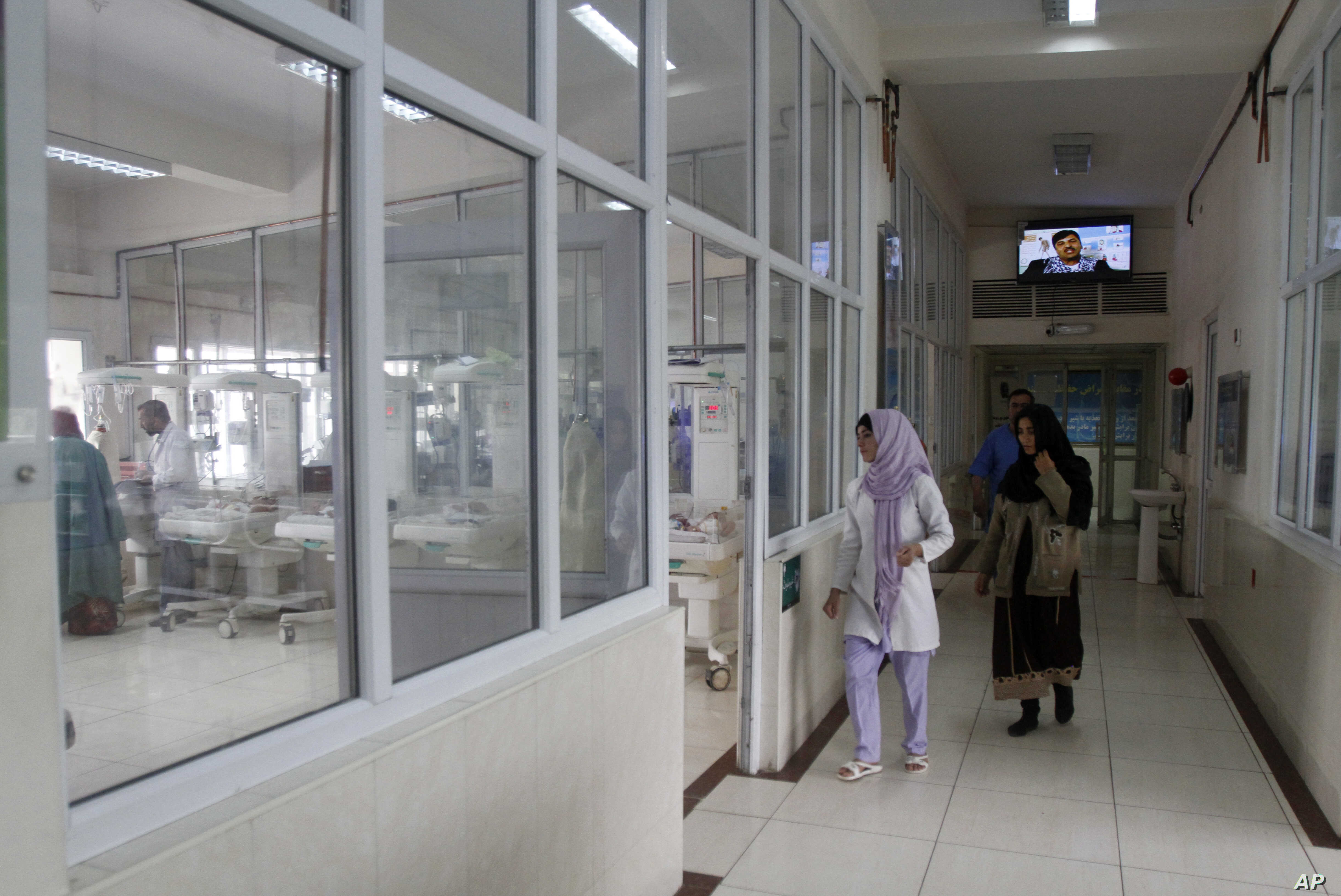 FILE - An Afghan doctor visits an infant ward at a hospital in Kabul, Afghanistan, May 7, 2015.