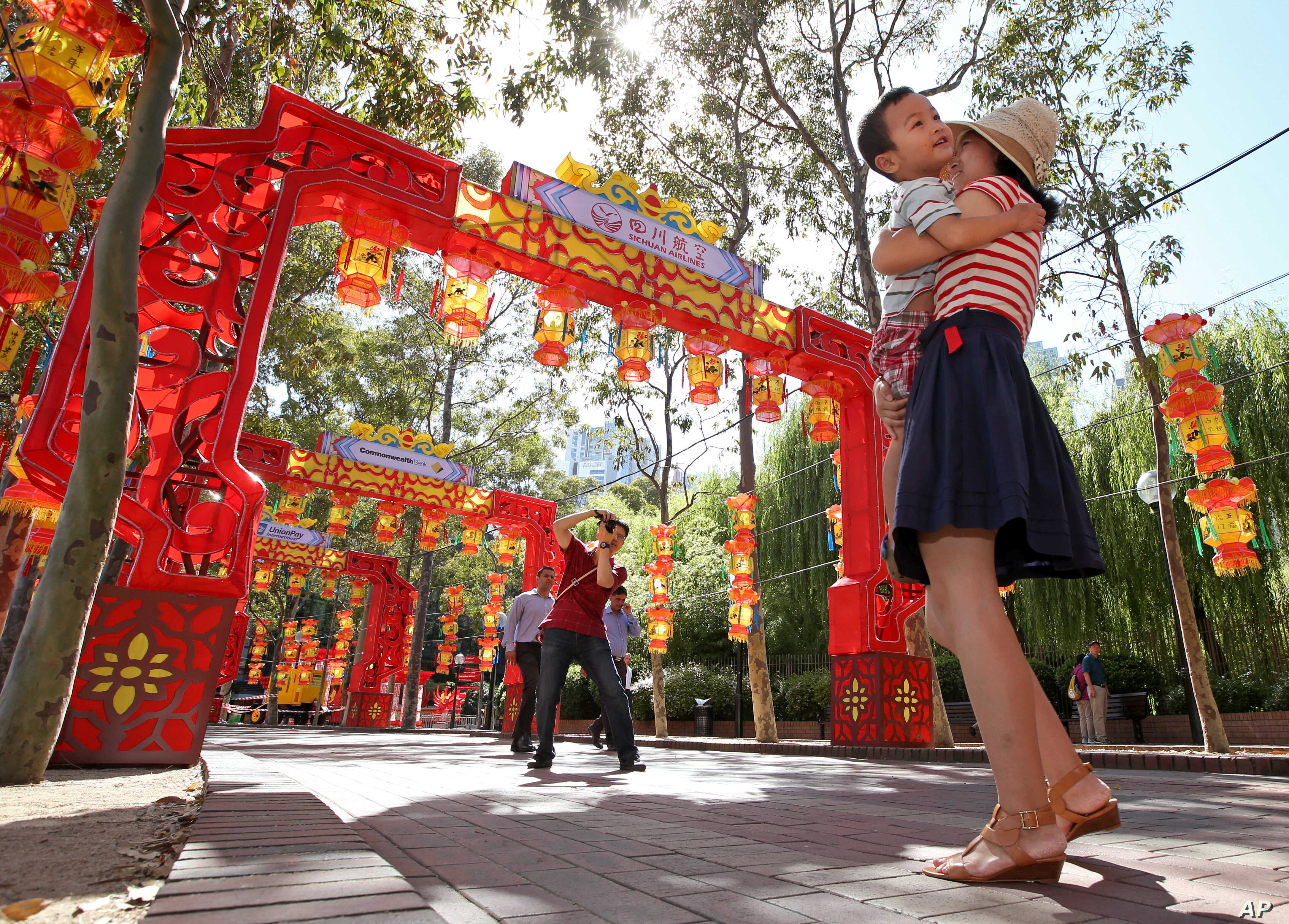 FILE -  Pen Pu, center, photographs his wife Chelsea Peng, right, and their three-year-old son Dore Peng, amongst a colorful display of arches and lanterns near the Chinese Garden of Friendship in Sydney, Australia.