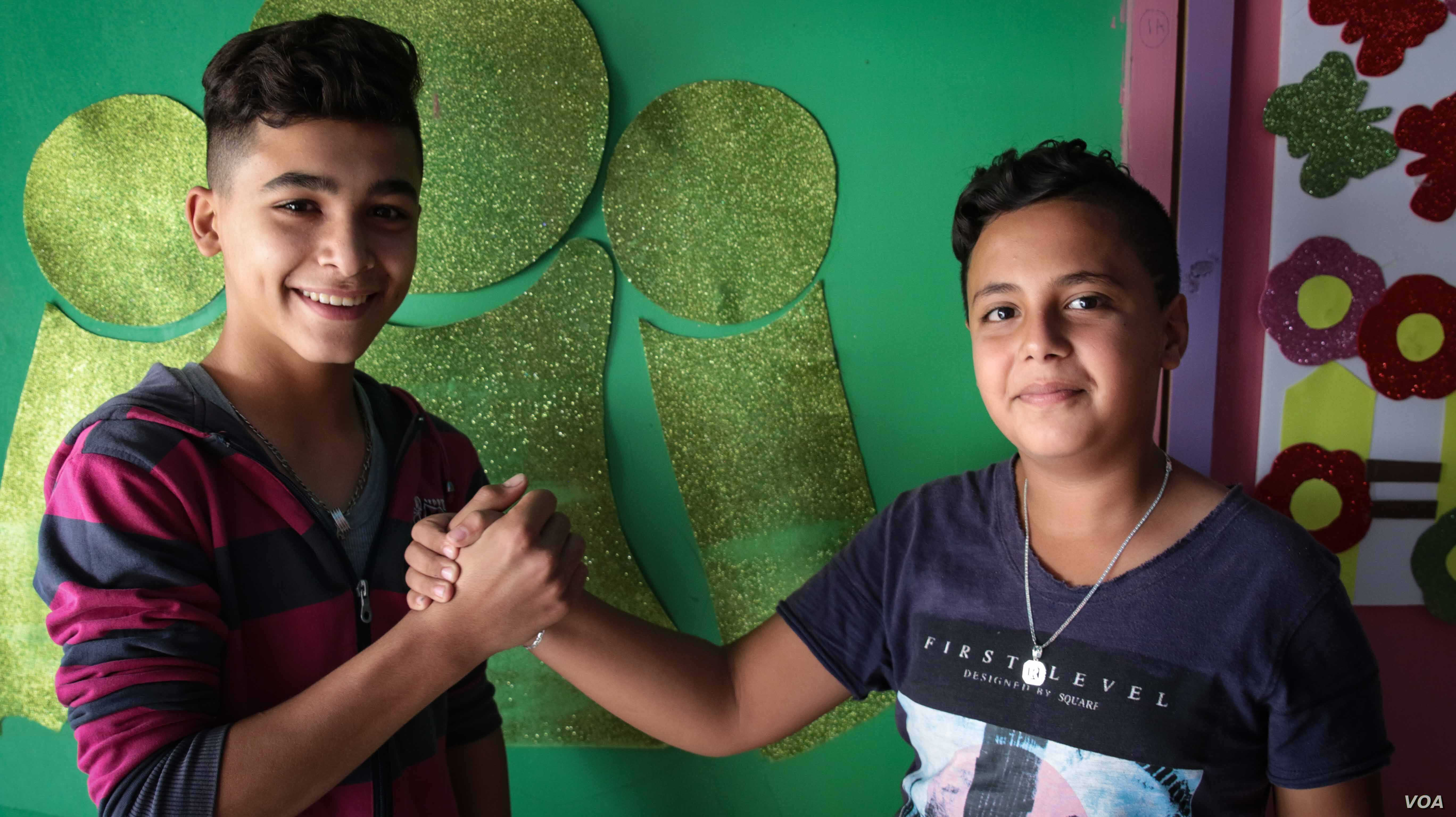 Jibril Latach, left, 16, is Lebanese and met his friend Raed, 14, a Syrian refugee, at the Beyond Association center where the choir practices.