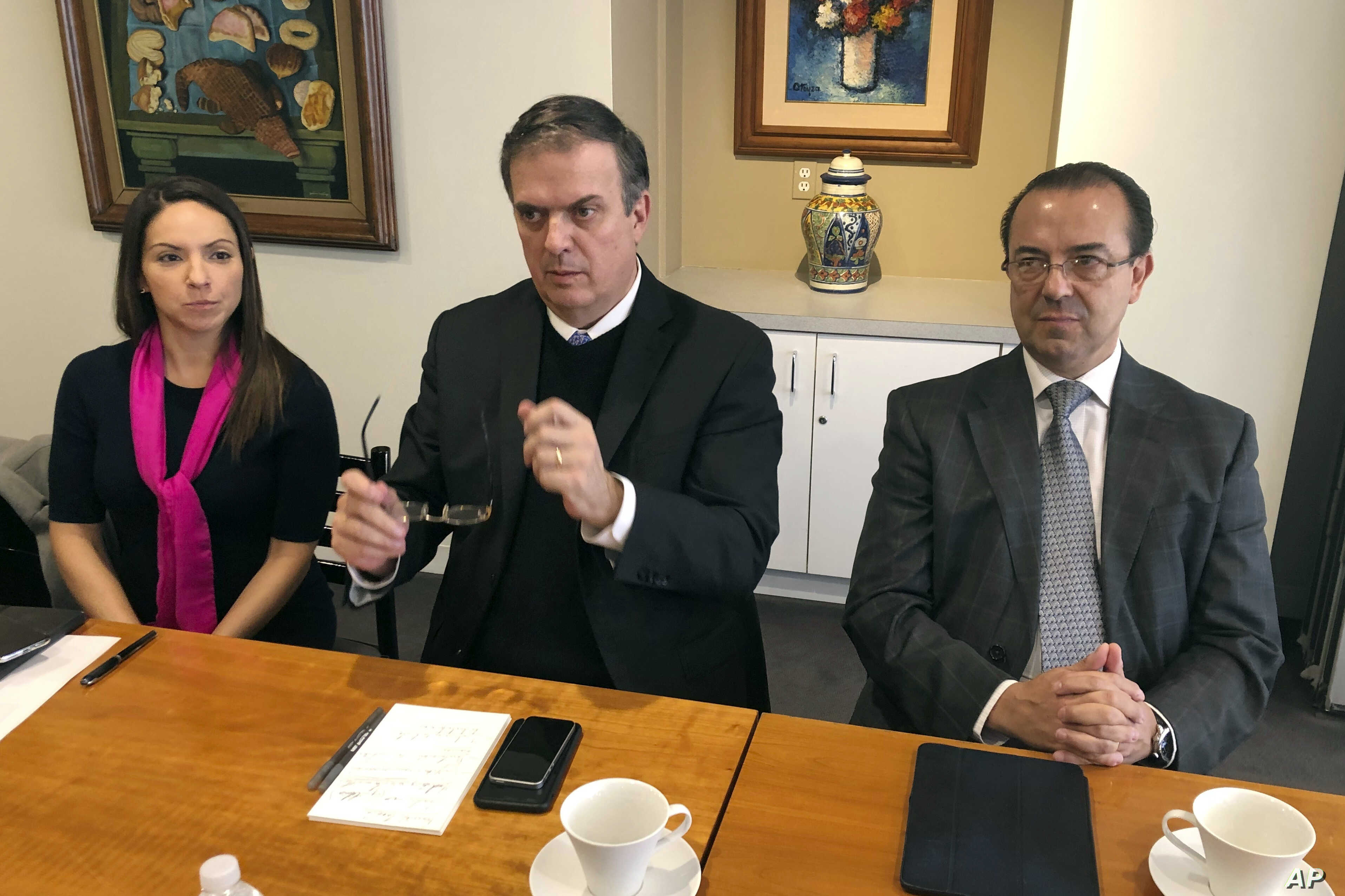 Mexican Foreign Minister Marcelo Ebrard, center, talks to reporters, Dec. 3, 2018, at the Mexican Embassy in Washington.