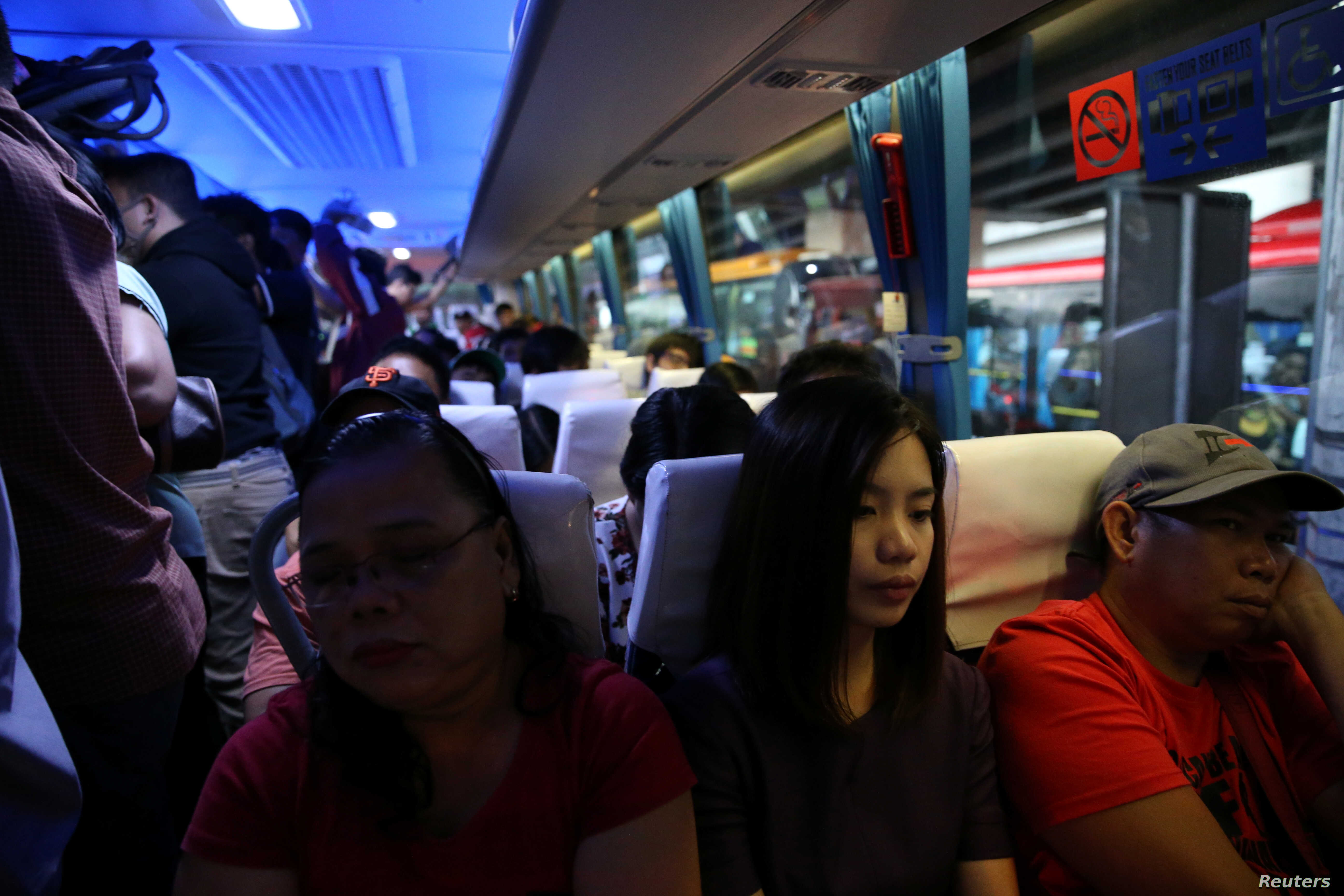 Janice Sarad, 22, who works for a bank, rides a crowded bus going to work in Cubao, Quezon City, Metro Manila, Philippines, Nov. 26, 2018.