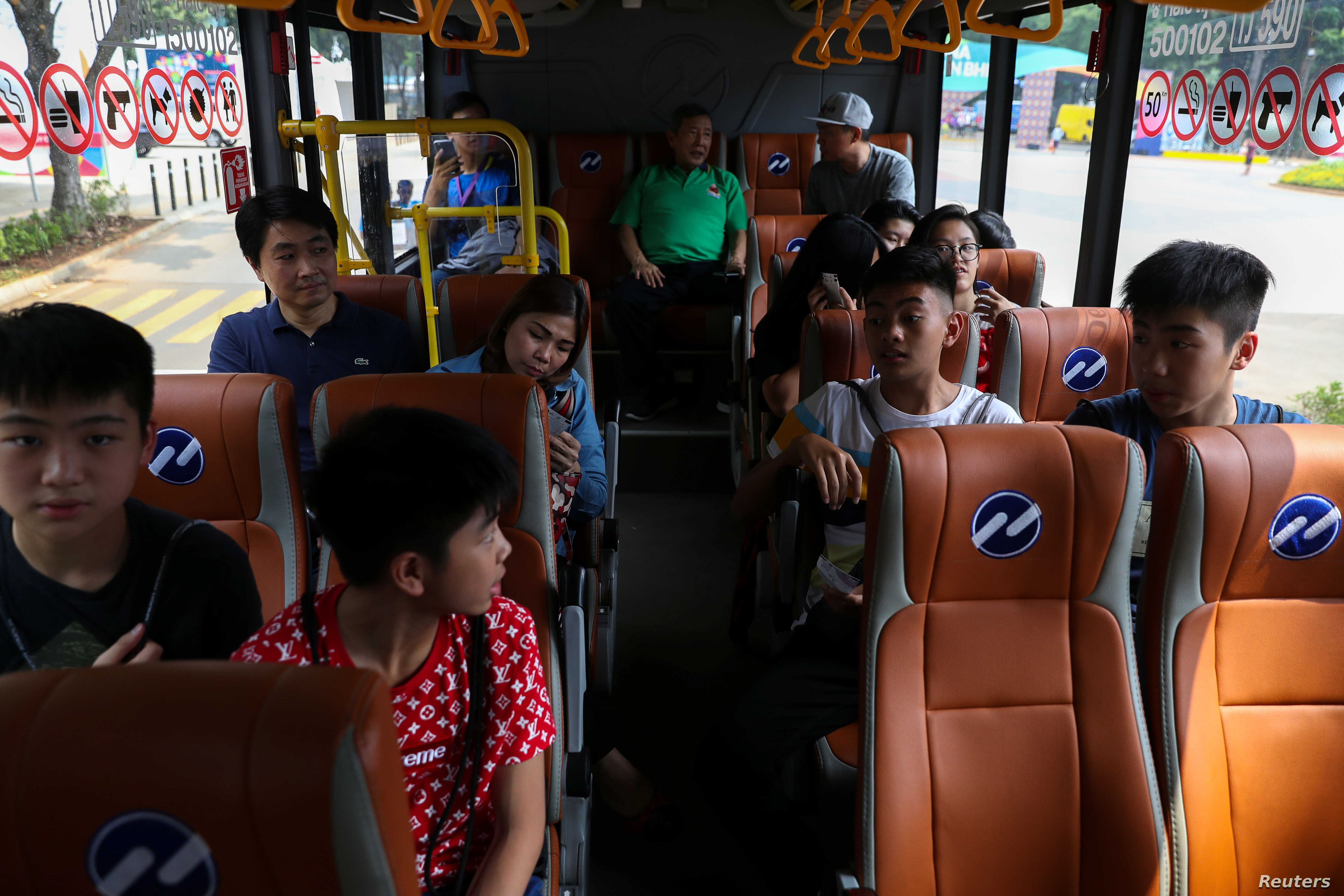 Spectators ride a shuttle bus inside the Gelora Bung Karno sports complex, ahead of the 2018 Asian Games in Jakarta, Indonesia, Aug. 17, 2018.