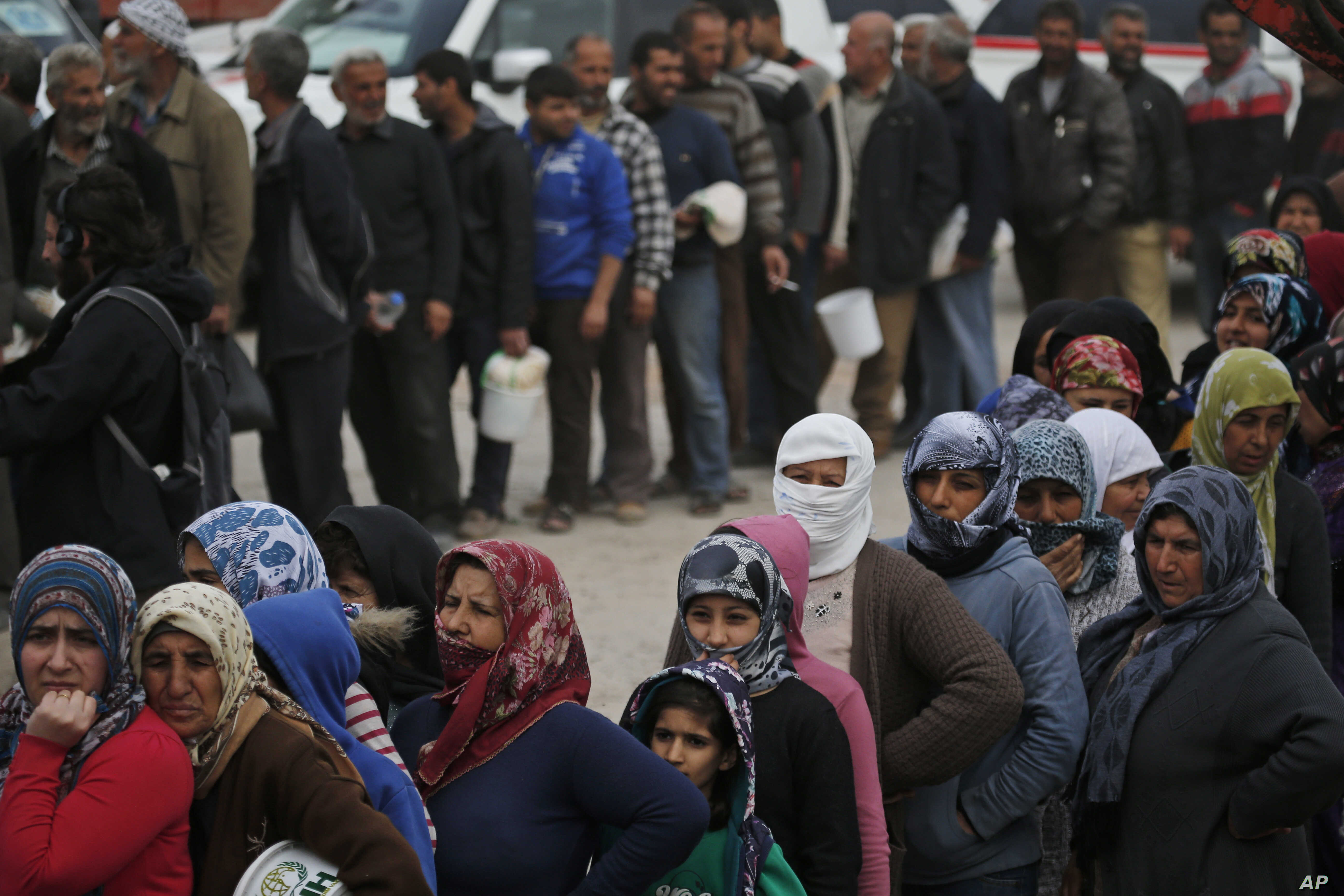 Syrians line up for food at a distribution center in the northwestern city of Afrin, Syria, during a Turkish government-organized media tour into northern Syria, March 24, 2018.