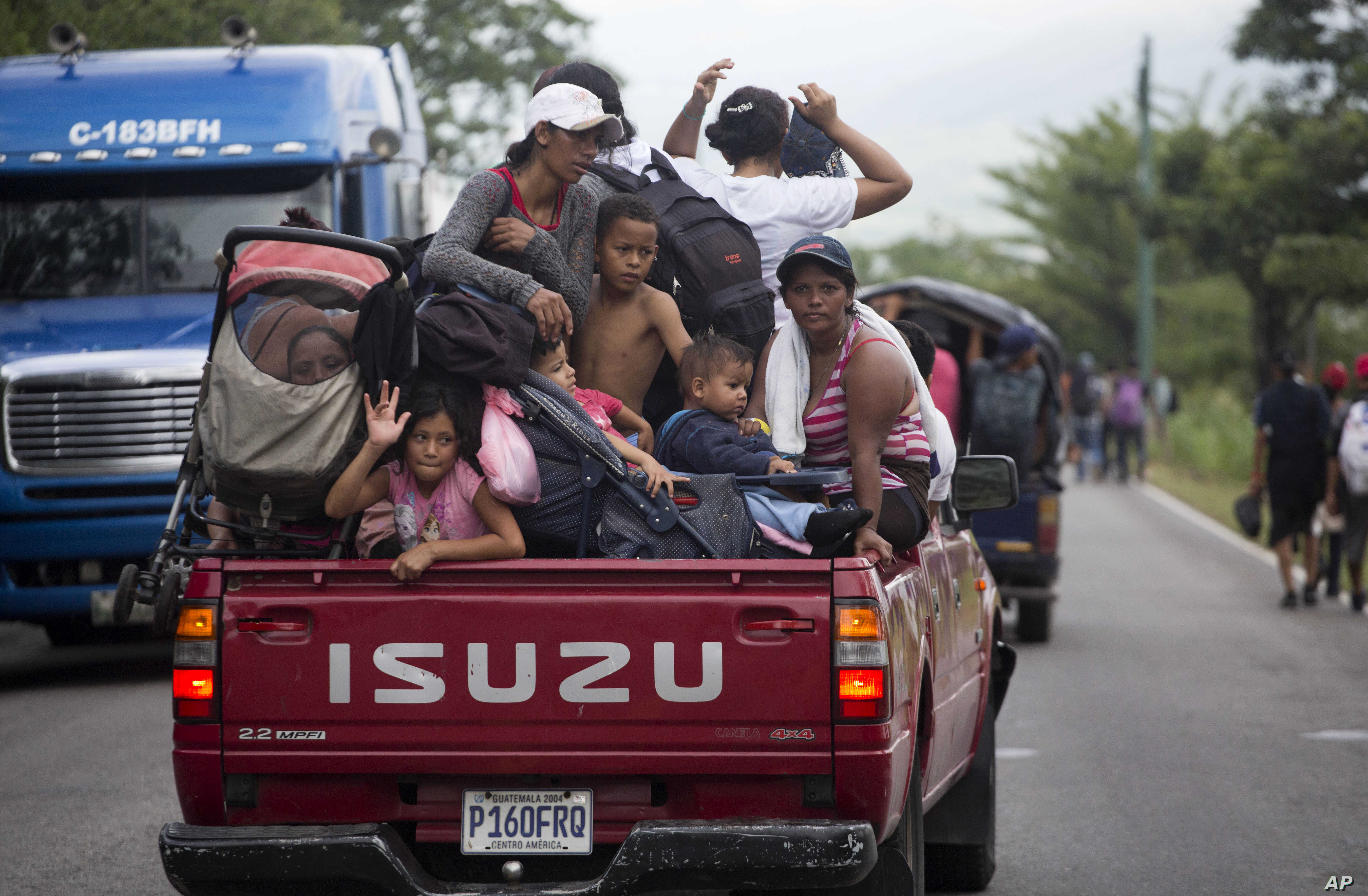 Honduran migrants who are traveling to the U.S. as a group get a free ride in the back of a truck as they make their way through Zacapa, Guatemala, Oct. 17, 2018.