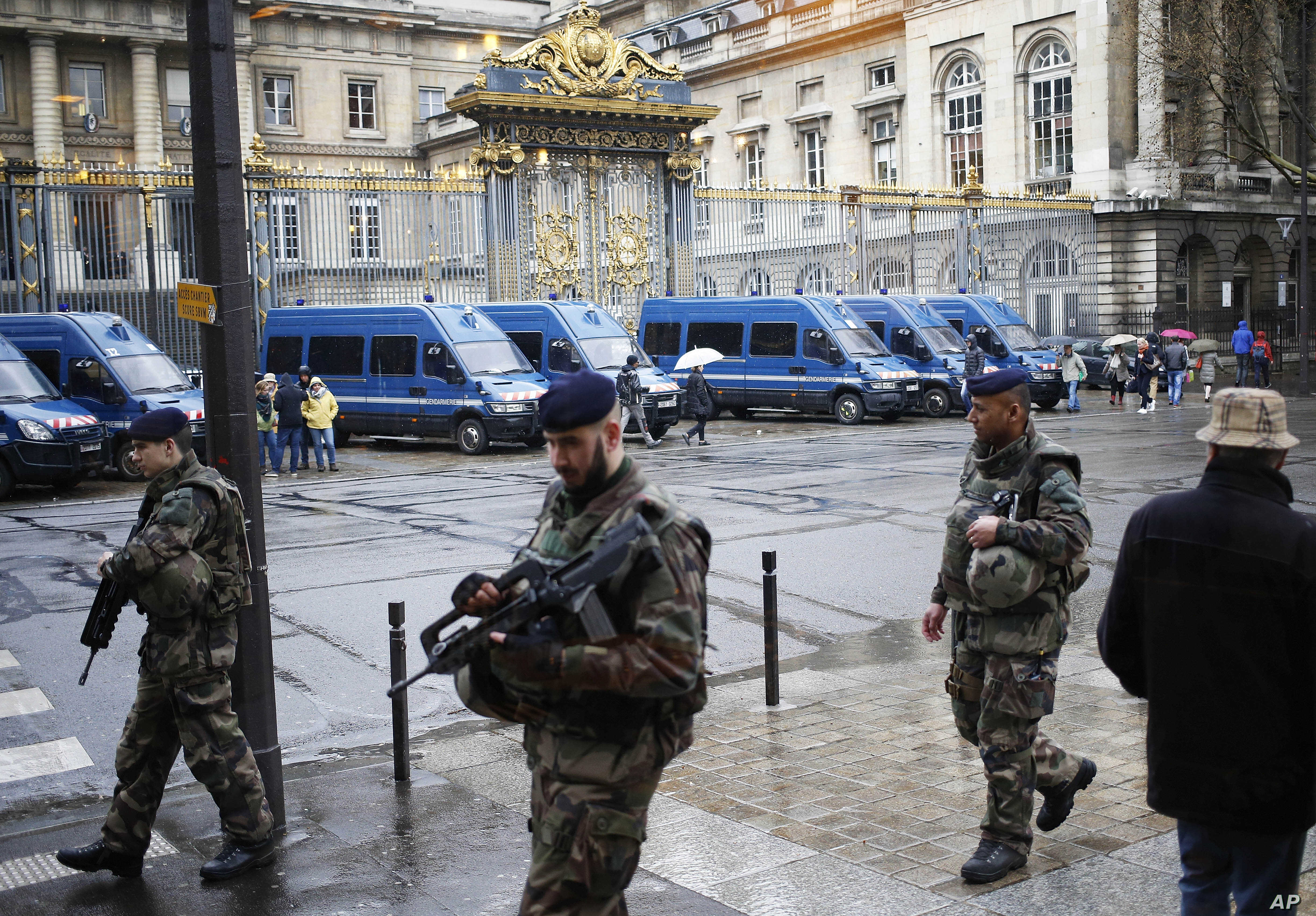 French soldiers patrol outside the Paris hall of Justice, March 30, 2016 while Frenchman Reda Kriket  is being questioned by a magistrate who is expected to file preliminary terrorism charges.