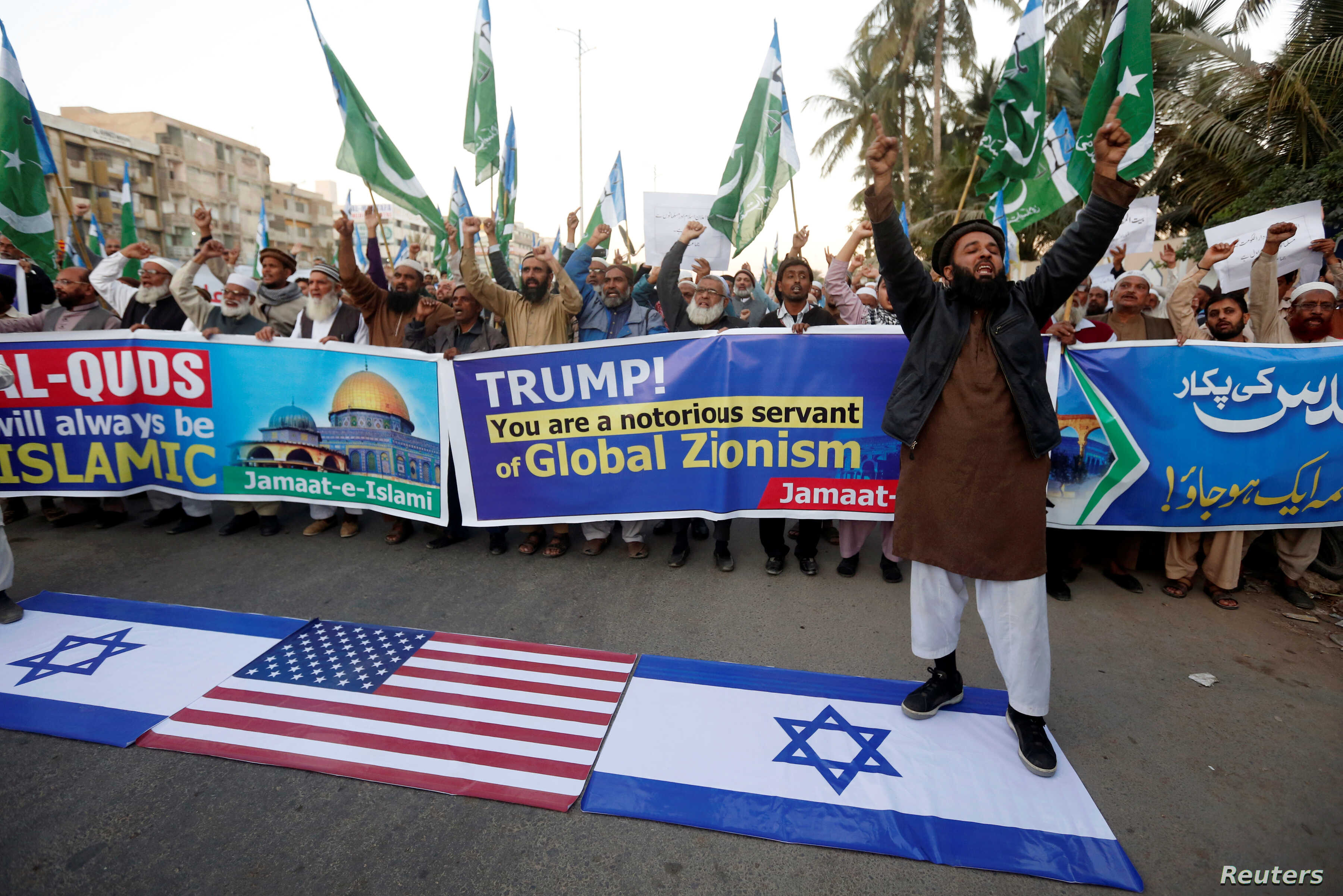 A supporter of religious and political party Jamaat-e-Islami (JI) chants slogans with others as he stands on Israeli flag during a protest against U.S. President Donald Trump's decision to recognize Jerusalem as the capital of Israel, in Karachi, Pak...