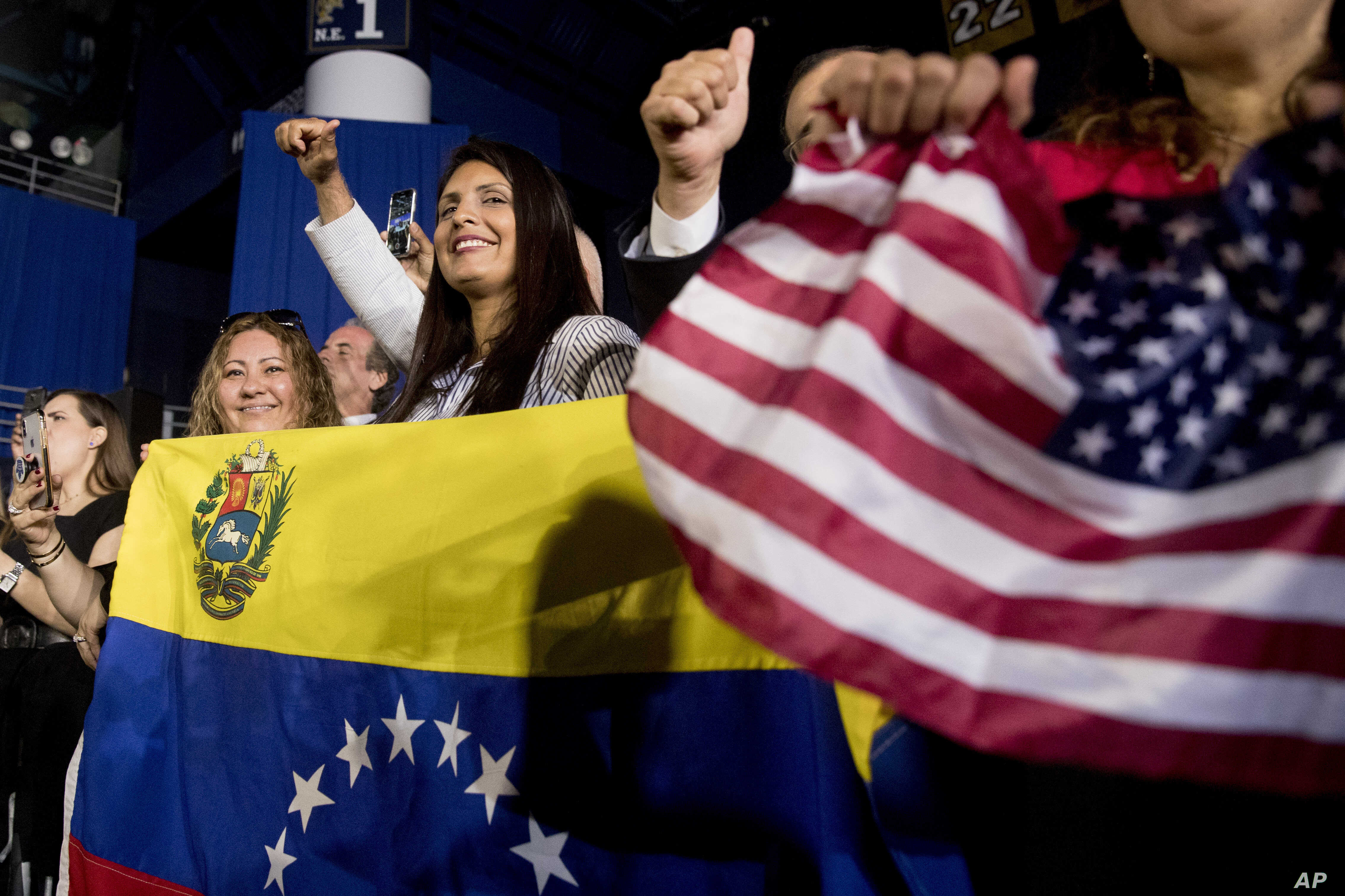Members of the audience wave Venezuelan and American flags as President Donald Trump speaks to a Venezuelan American community at Florida Ocean Bank Convocation Center at Florida International University in Miami, Feb. 18, 2019.