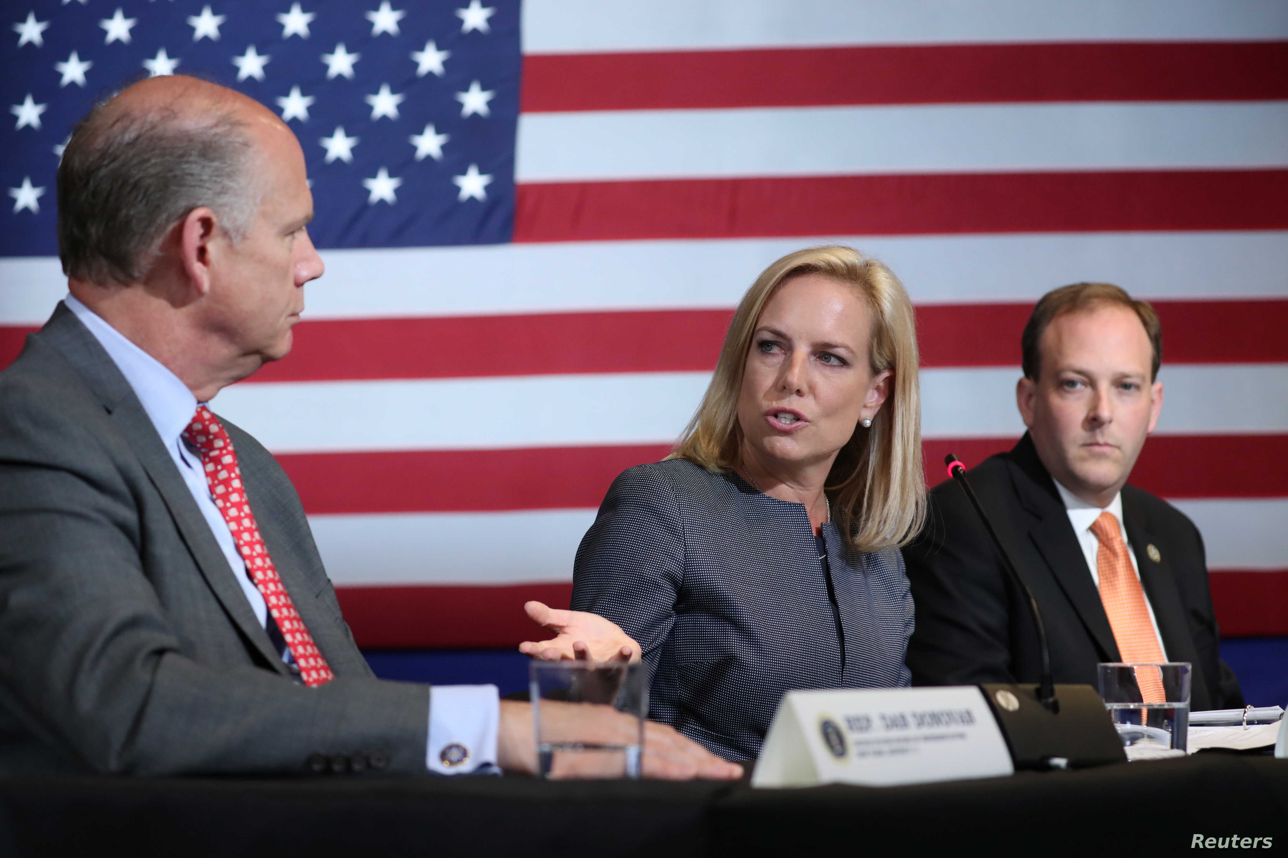 U.S. Secretary of Homeland Security Kirstjen Nielsen gestures toward U.S. Rep. Dan Donovan, R-N.Y., as she sits between Donovan and Rep. Lee Zeldin, R-N.Y., during a discussion on immigration and the gang MS-13 with U.S. President Donald Trump at the...