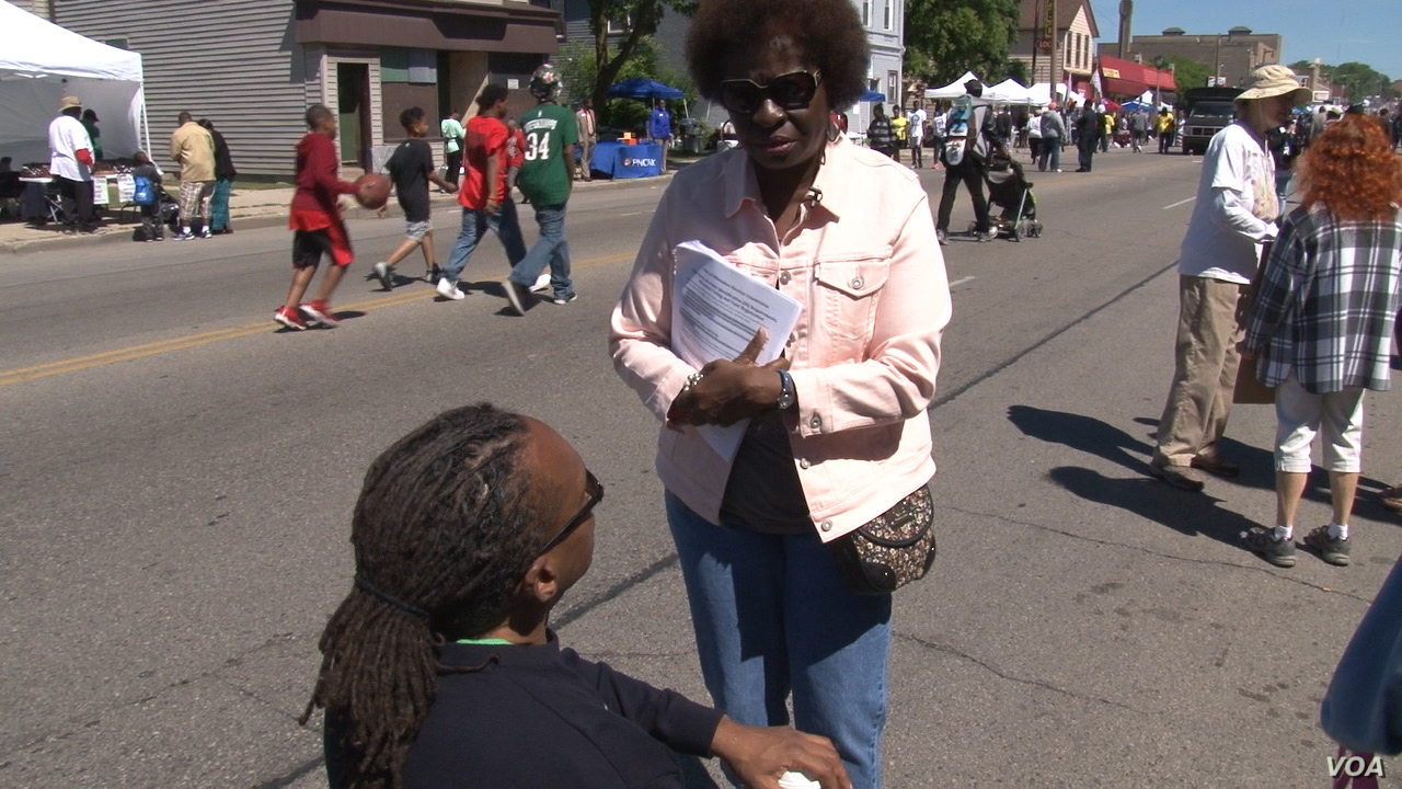 Anita Johnson, who works with the Democracy 2020 coalition in Wisconsin, discusses voting law changes at a Milwaukee street festival in June. (J. Swicord/VOA)
