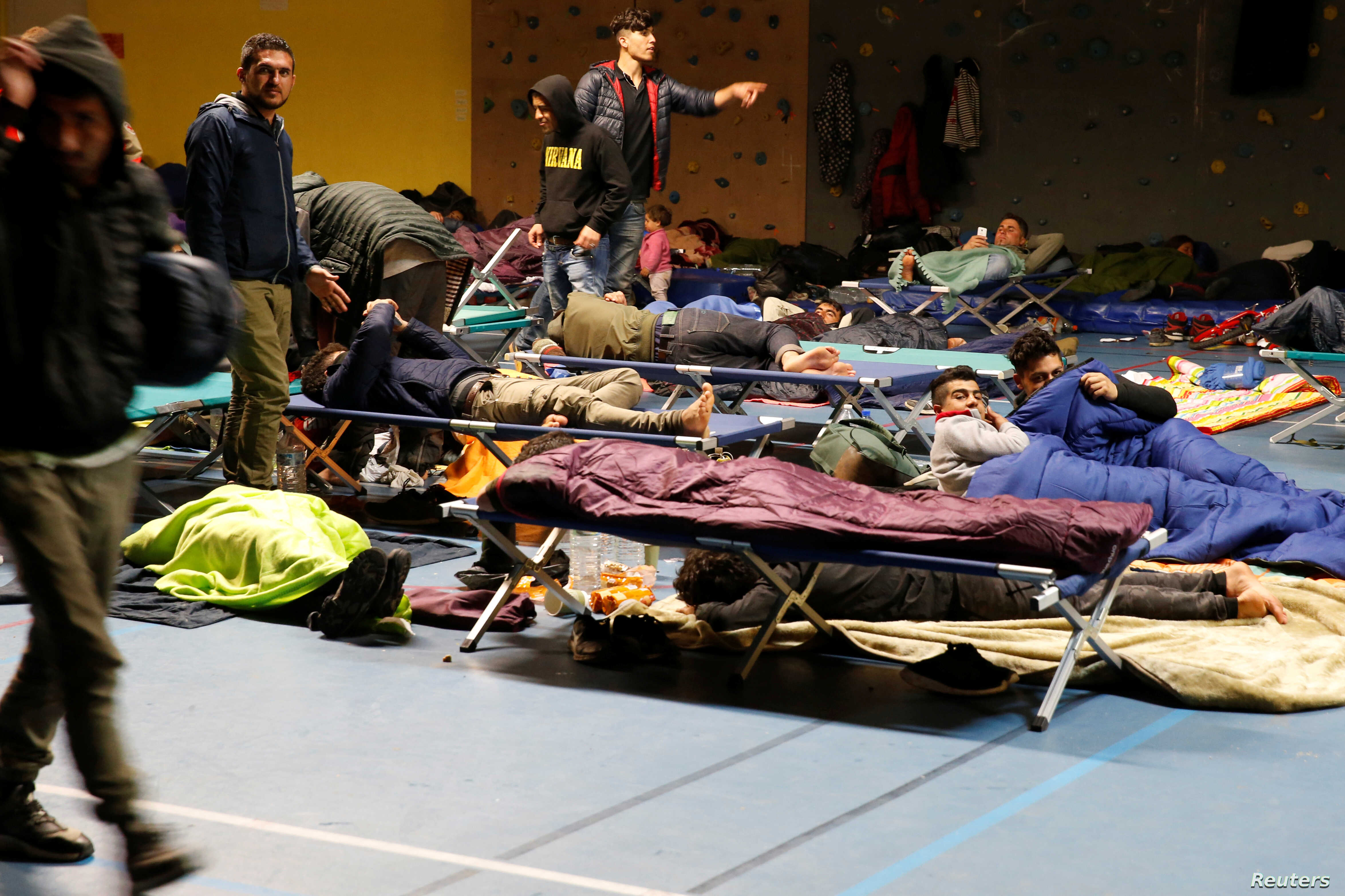 Migrants sleep in a gym after a big fire which destroyed many wood houses at a camp for migrants in Grande-Synthe near Dunkirk, France, April 11, 2017.