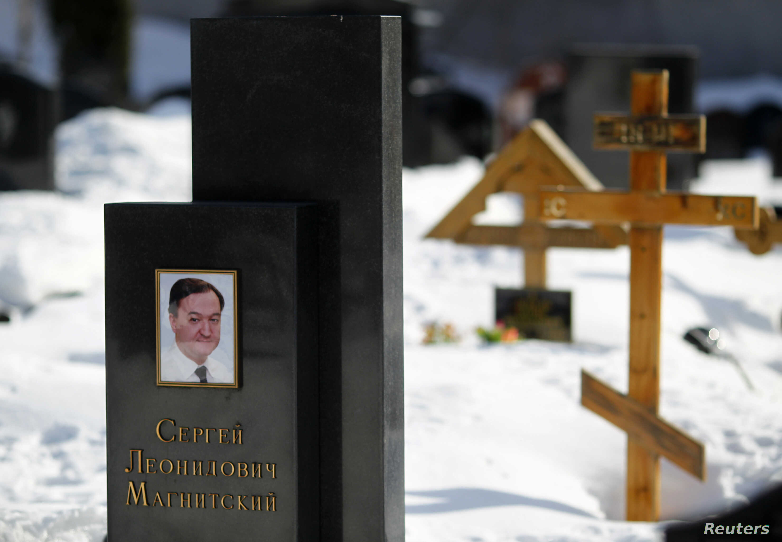 A picture of lawyer Sergei Magnitsky is seen on his grave in the Preobrazhensky cemetery in Moscow March 11, 2013. A Russian court on Monday postponed until March 22 the start of the posthumous trial of a whistleblowing lawyer, Magnitsky, which human...