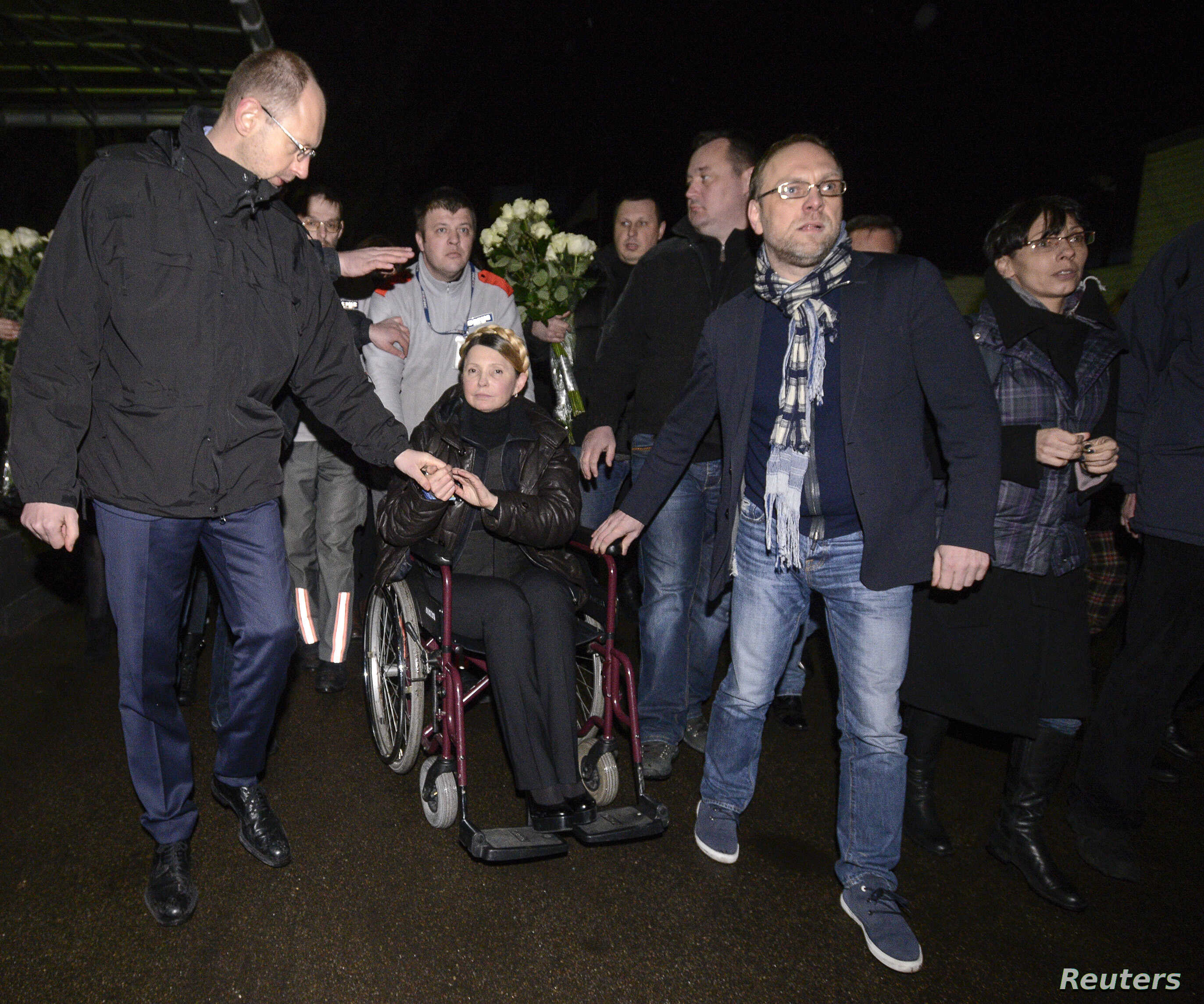 Ukrainian opposition leader Yulia Tymoshenko (C) is transported on a wheelchair upon her arrival at the airport in Kyiv, Feb. 22, 2014.
