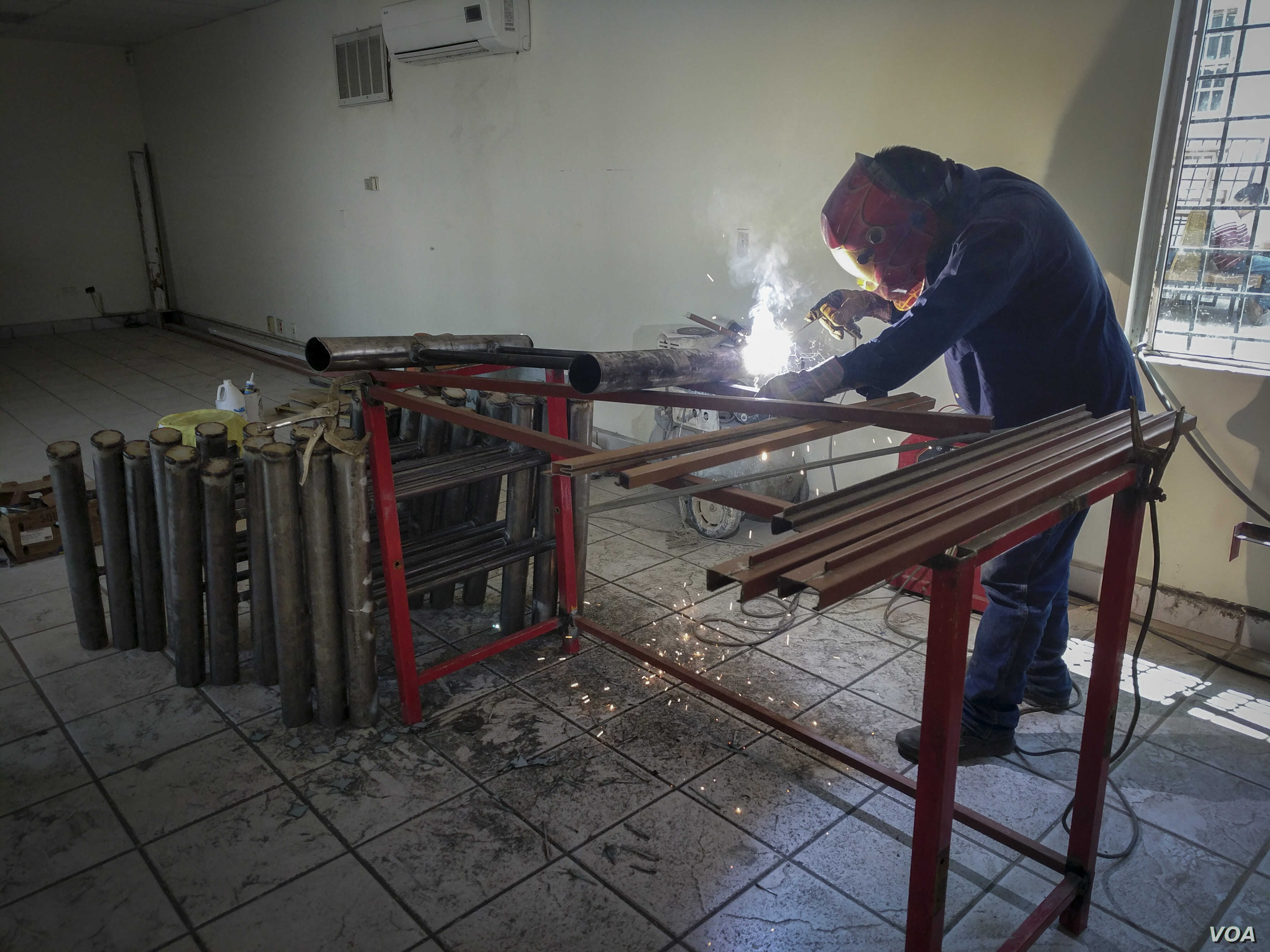 A welder is seen assembling beds at Alfa y Omega migrant shelter in Mexicali, Mexico, in preparation for the Central American caravan. (R. Taylor/VOA)