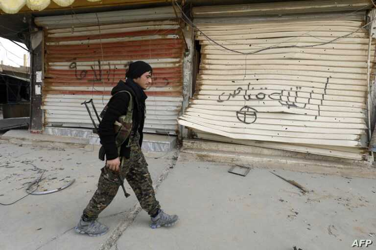"""A fighter from the Syrian Democratic Forces (SDF) walks past shops with their fronts painted with the Arabic phrases """"beware a sniper"""" and """"caliphate state"""", in the city of Hajin in Syria's eastern Deir Ezzor province, Jan. 27, 2019."""