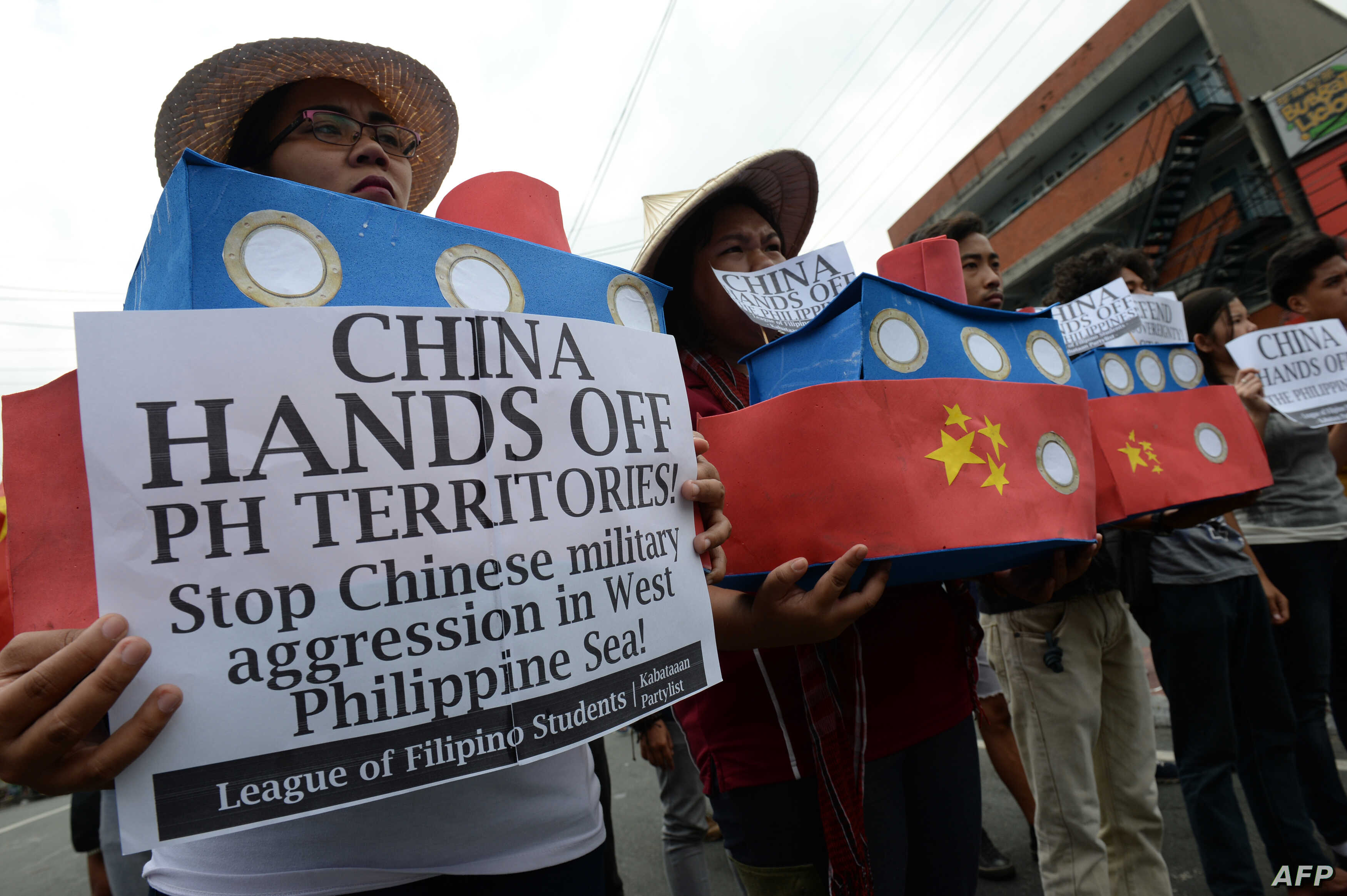 Filipino students hold replicas of Chinese maritime surveillance ships as they shout anti-Chinese slogans during a rally near Malacanang Palace in Manila on March 3, 2016, to denounce reported Chinese vessels dropping anchor near a South China Sea at...