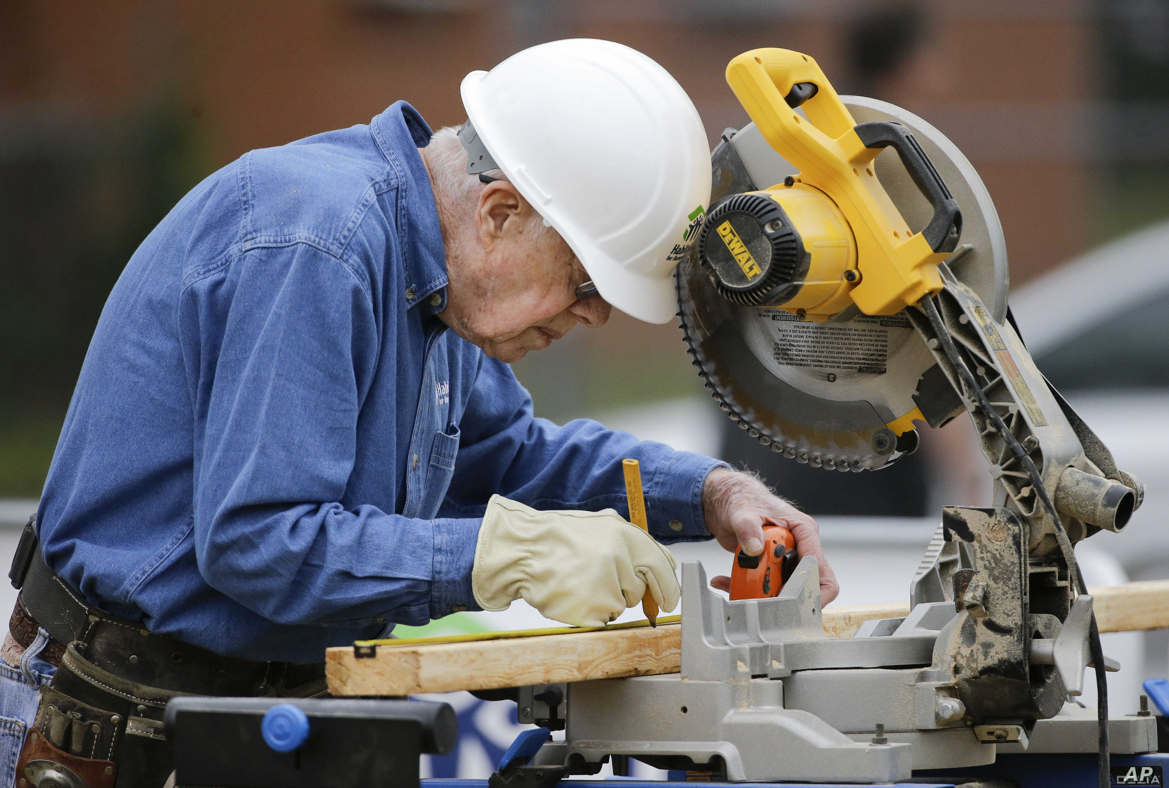 Former president Jimmy Carter measures before making a cut with a miter saw at a Habitat for Humanity building site, Nov. 2, 2015, in Memphis, Tennessee.