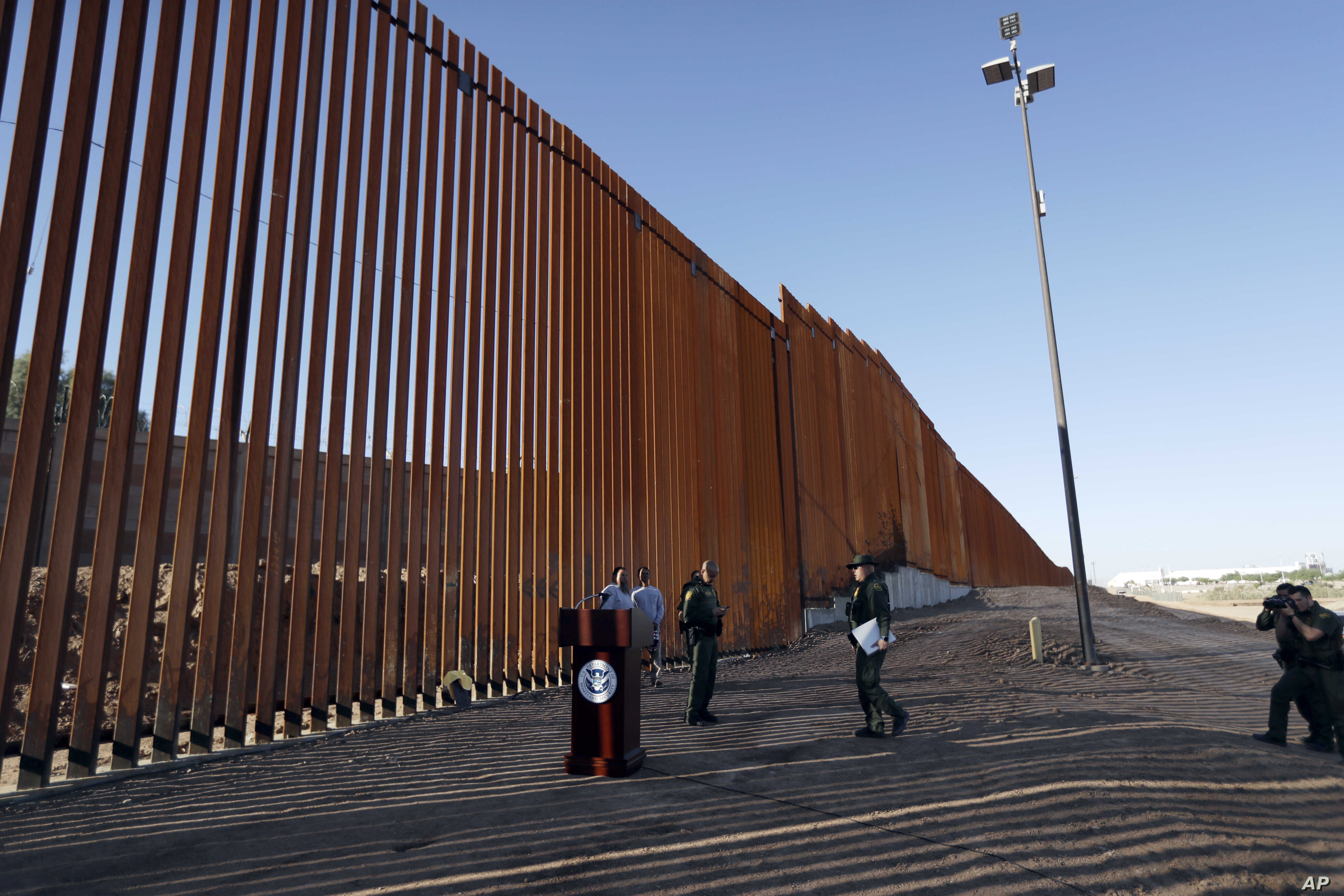 Border Patrol agents and others stand next to a new stretch of border wall in Calexico, Calif., Oct. 26, 2018.