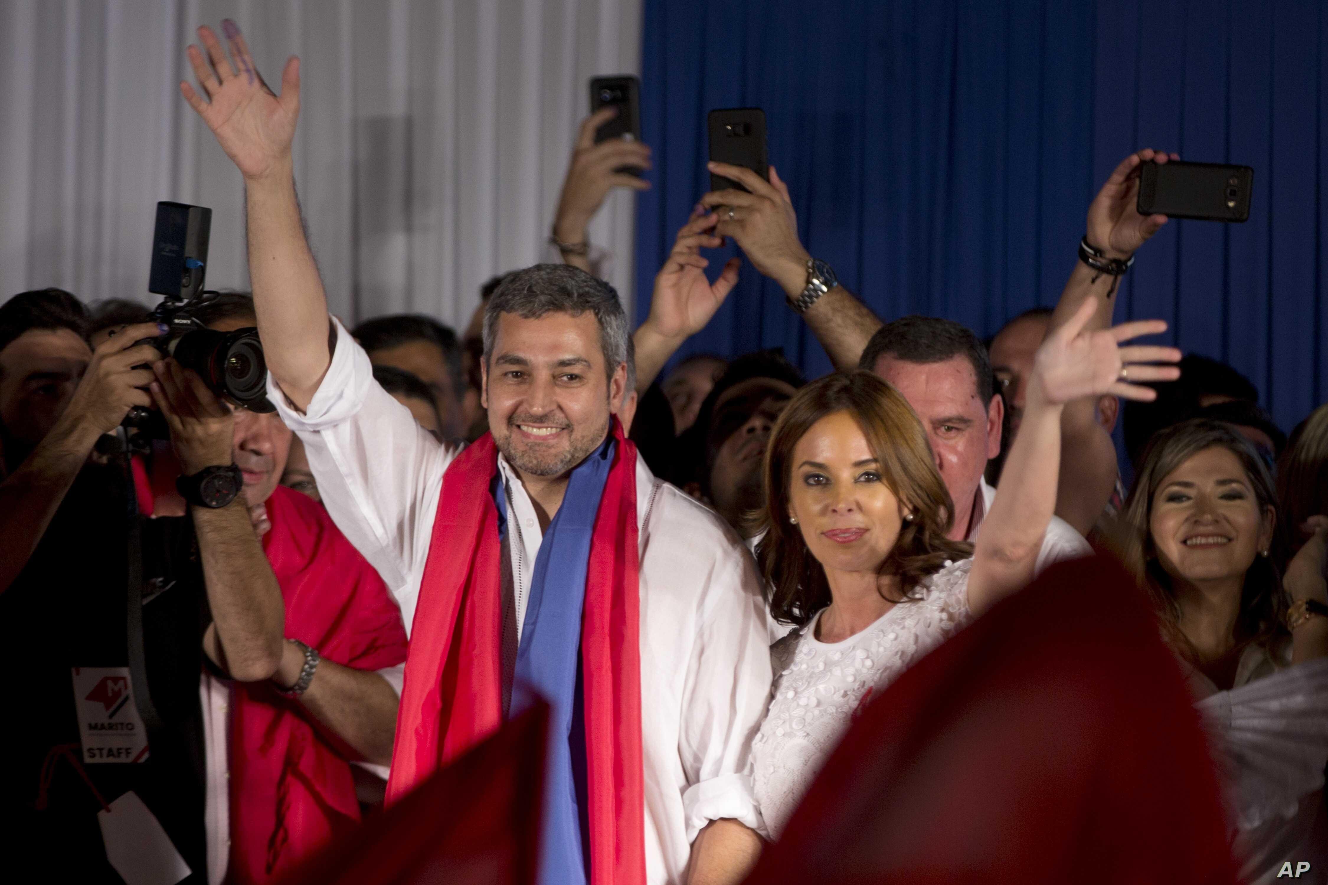 Paraguay's President Elect Mario Abdo Benitez. left, of Colorado Party, and his wife Silvana Lopez Moreira wave at supporters during celebrations at the party headquarter's in Asuncion, Paraguay, Sunday, April 22, 2018.