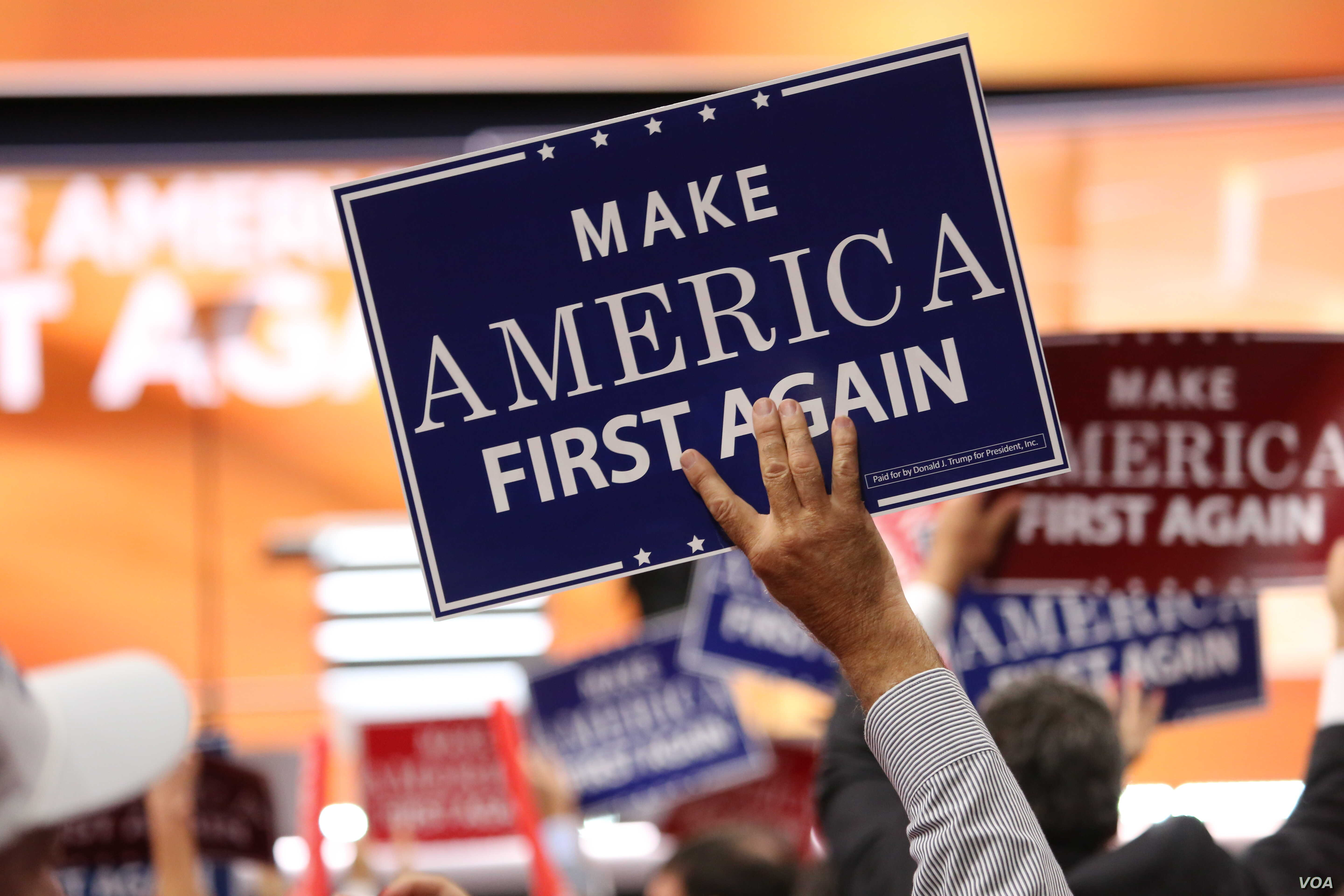 "Delegates hold ""Make America First Again"" posters on the Republican National Convention floor in Cleveland, Ohio, July 20, 2016. (Photo: Ali Shaker / VOA)"
