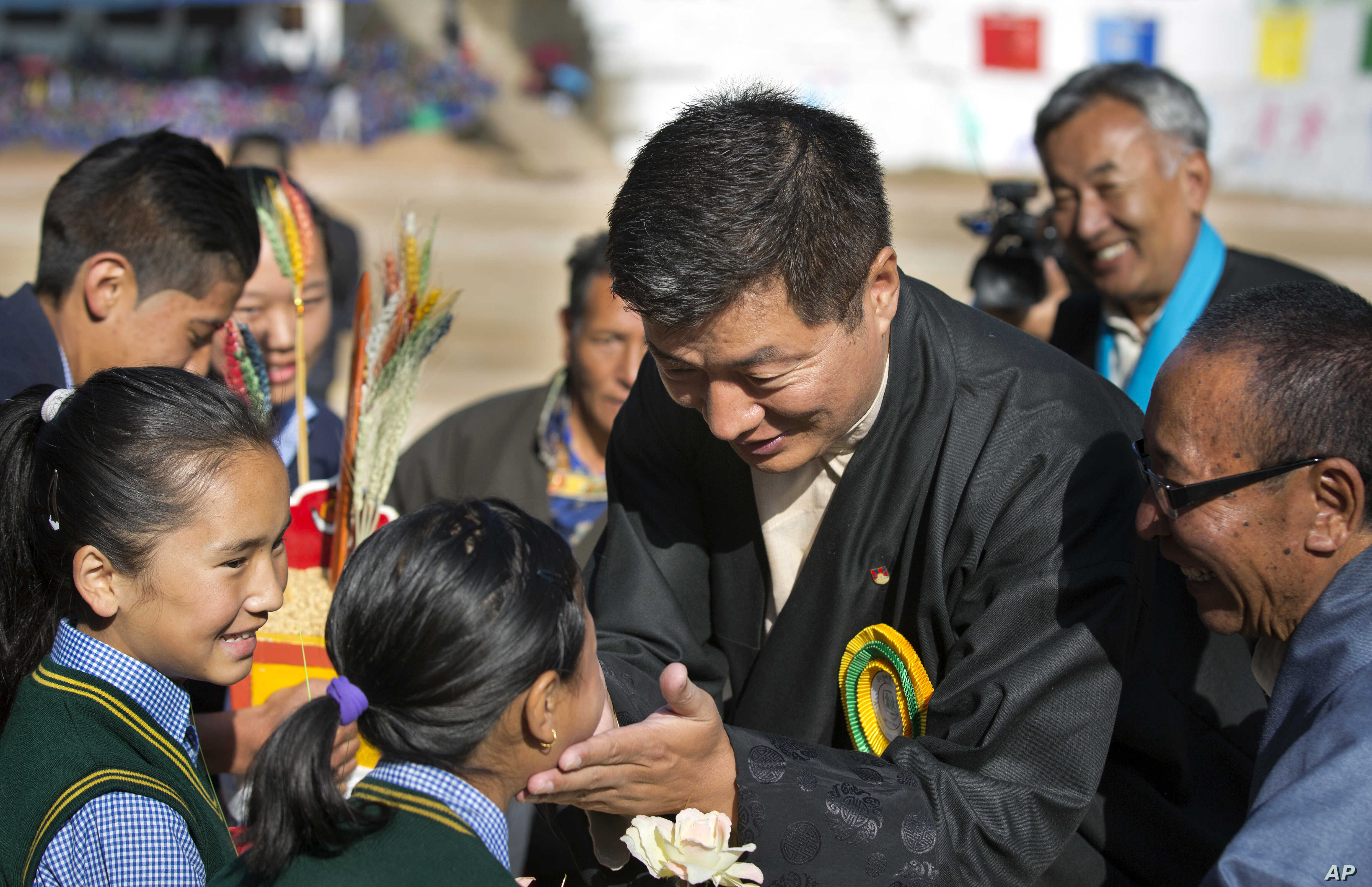 FILE - President of the Tibetan administration in exile Lobsang Sangay, center, greets a child as he arrives to attend the founding anniversary celebrations at the Tibetan Children's Village School in Dharmsala, India, Oct. 23, 2017.