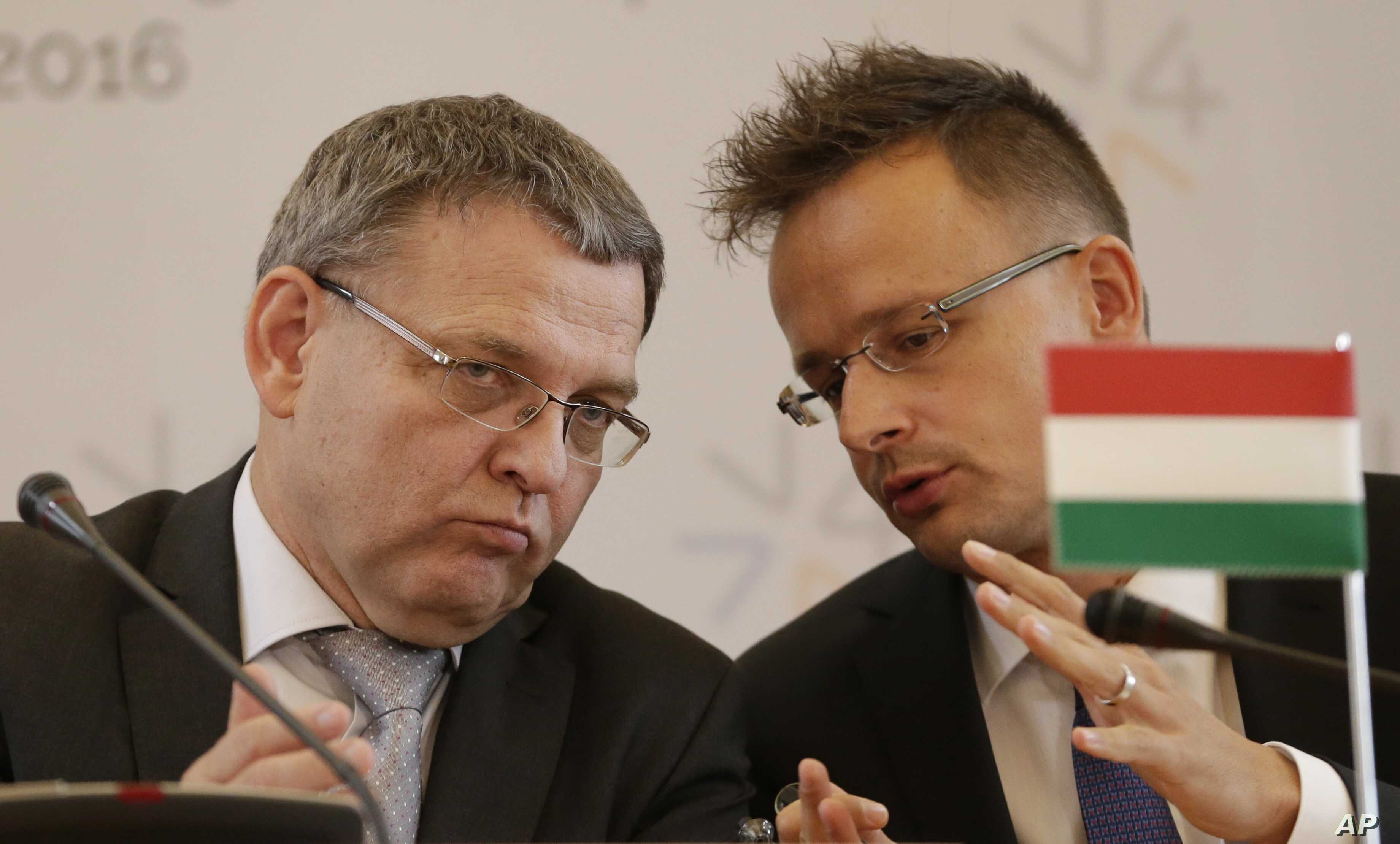Czech Republic's foreign minister Lubomir Zaoralek, left, talks to Hungary's foreign minister  Peter Szijjarto, right, during a press conference as the Visegrad Group foreign ministers meet their counterparts from Germany and Luxembourg to talk about...