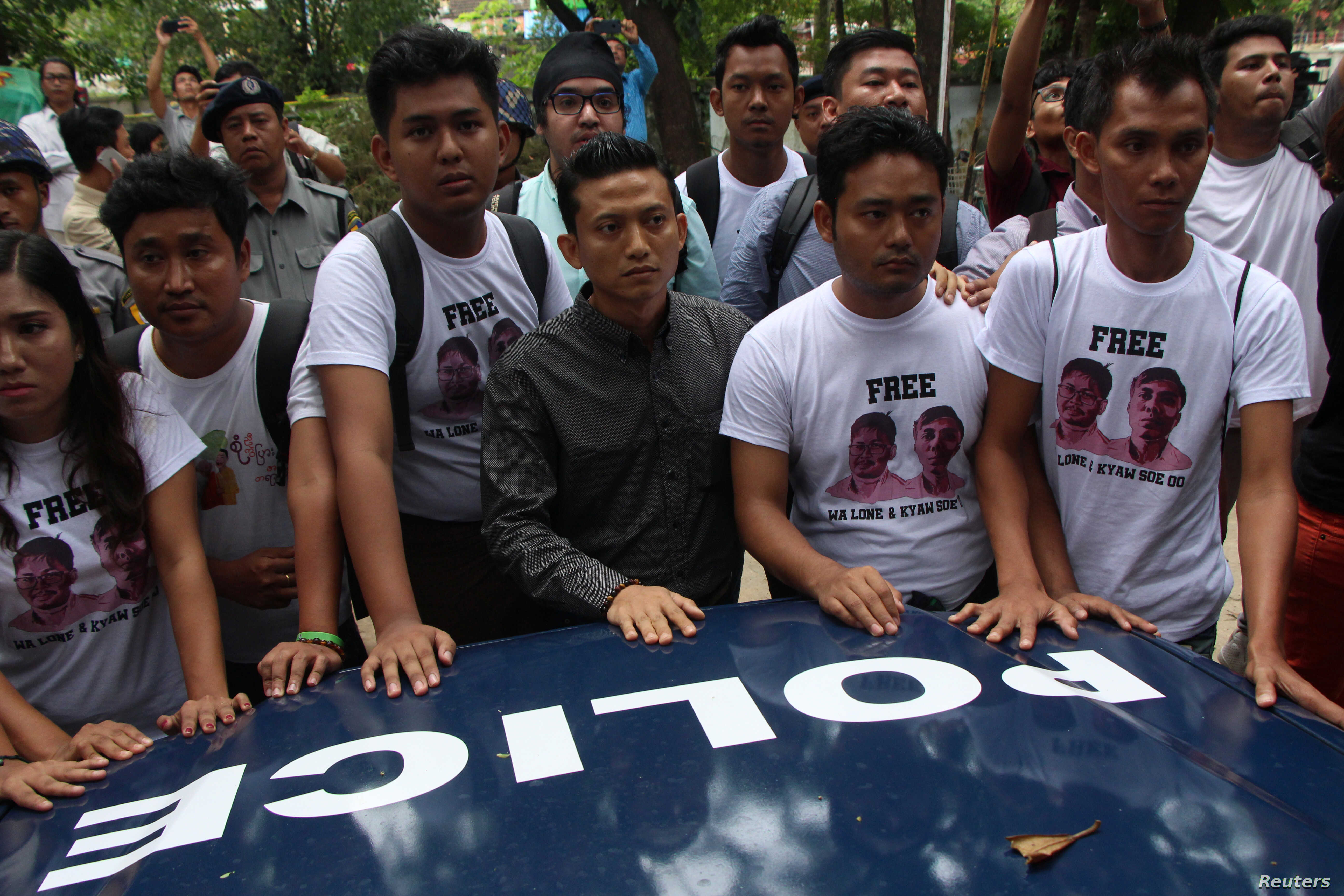 Myanmar journalists stand in front of a police vehicle transporting Reuters journalists Wa Lone and Kyaw Soe Oo to Insein prison after the court verdict in Yangon, Myanmar, Sept. 3, 2018.