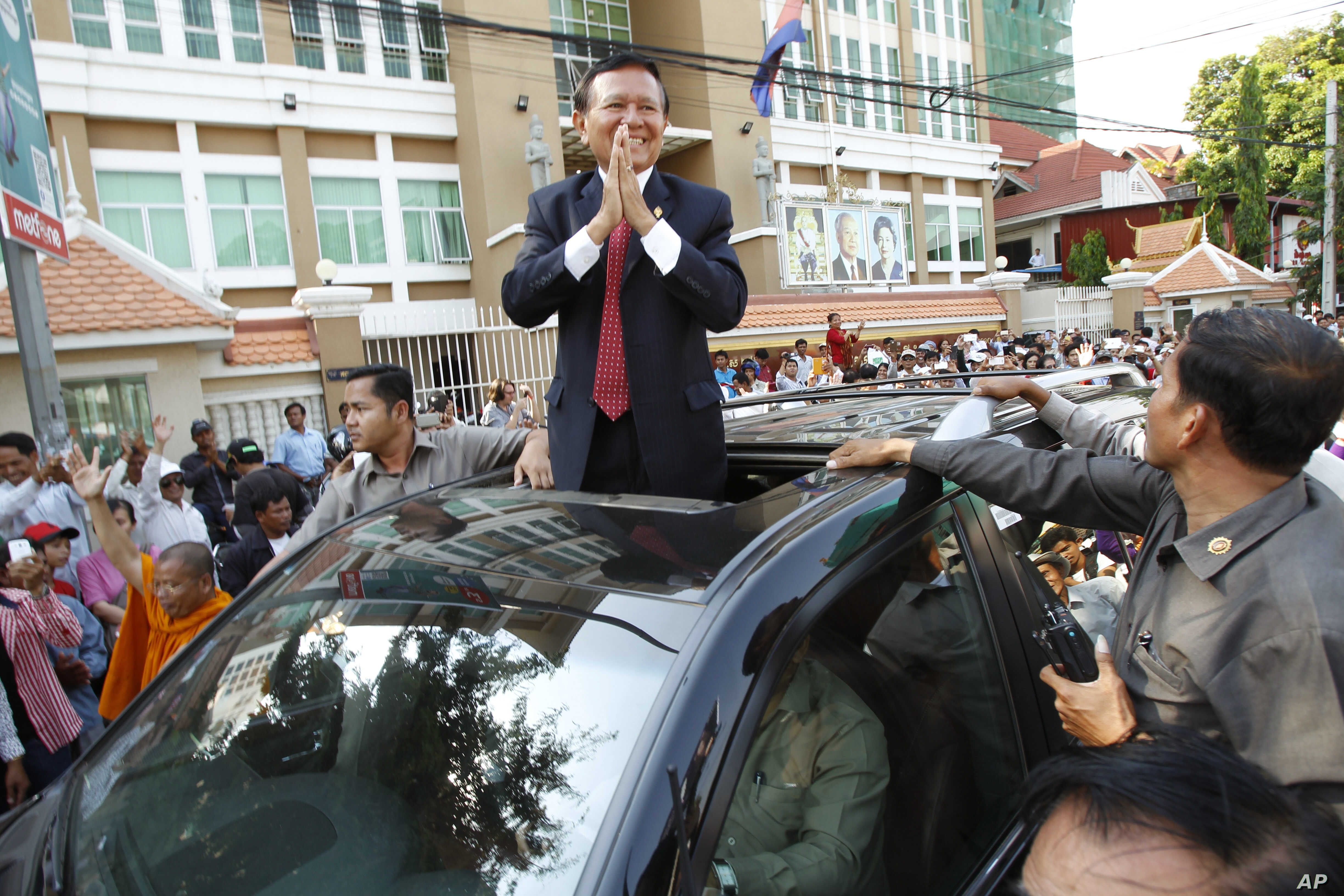 FILE - Cambodia's main opposition Cambodia National Rescue Party Deputy President and National Assembly Deputy President Kem Sokha greets to his supporters outside the Phnom Penh Municipality Court in Phnom Penh, Wednesday, April 8, 2015.