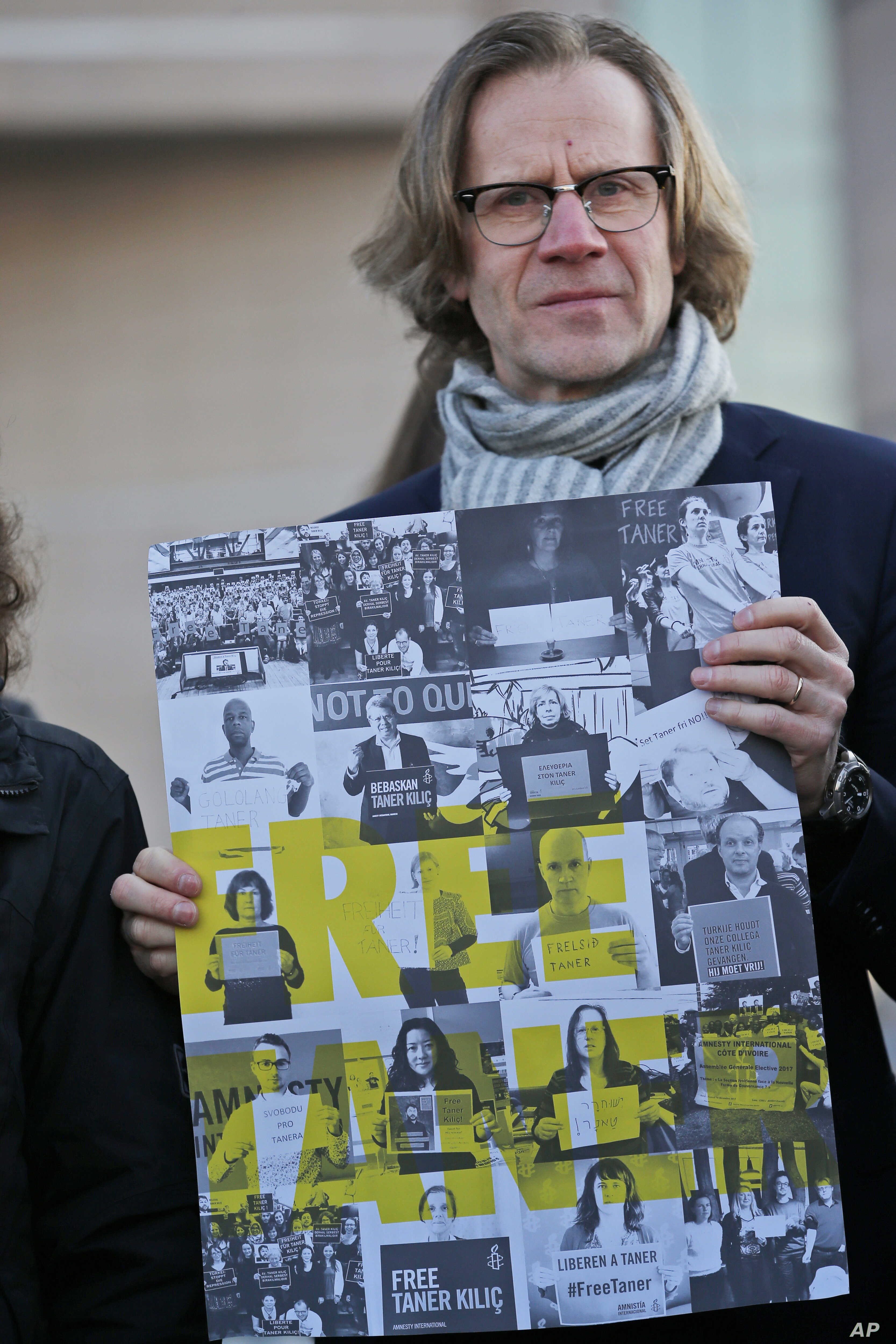FILE - Human rights activists stage a protest outside a court in Istanbul, Jan. 31, 2018  where eleven human rights activists, accused of belonging to and aiding terror groups, stood trial.