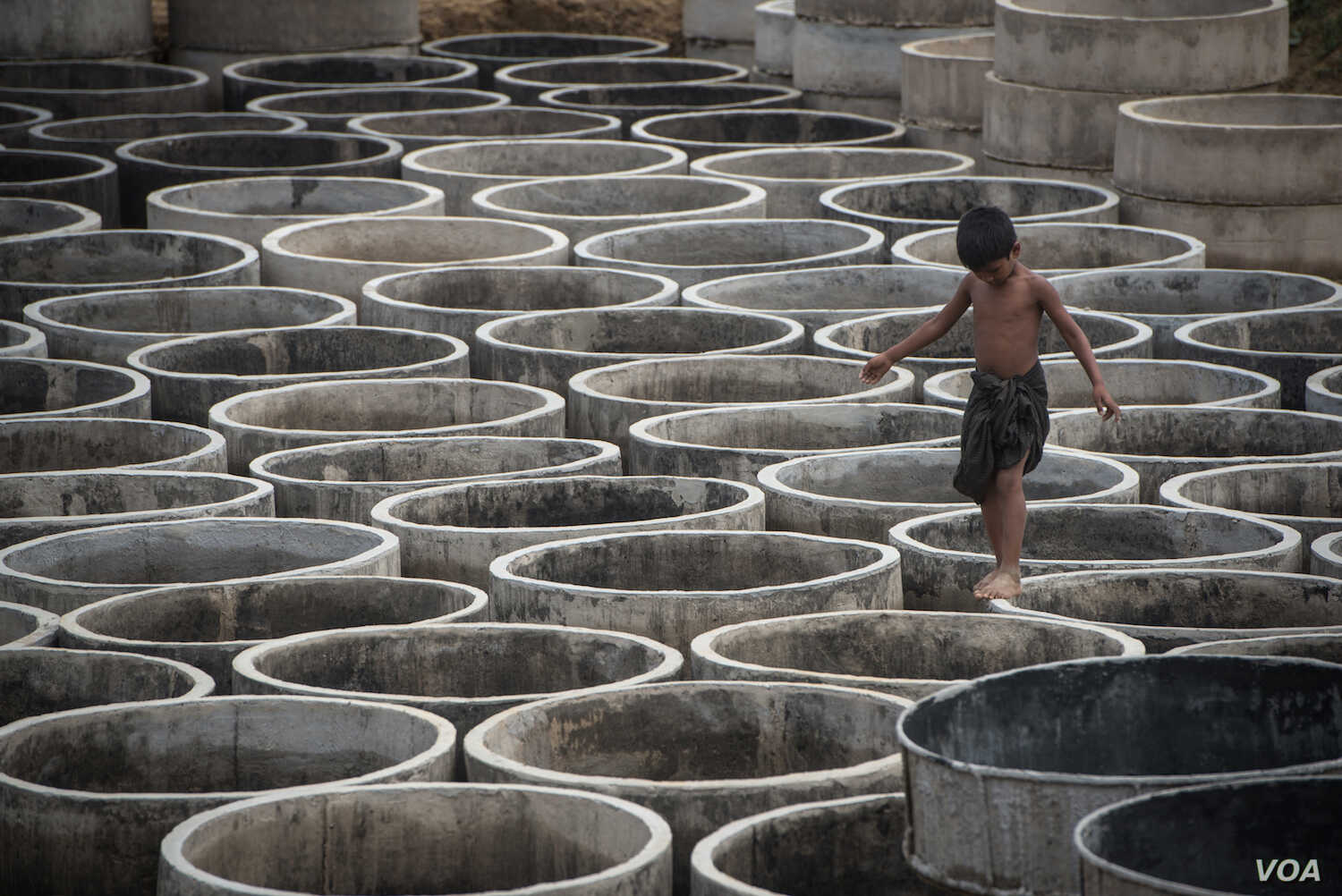 A Rohingya refugee child walks among concrete rings to be used for drainage in preparation for the annual rainy season in Bangladesh refugee camps.