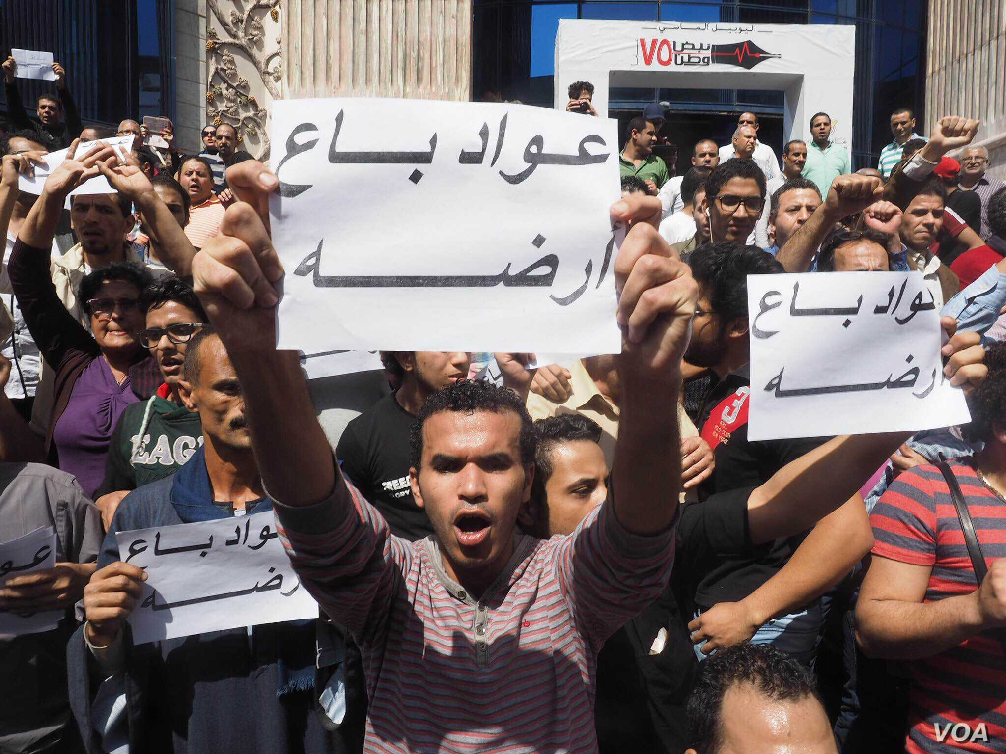 """Egyptian protesters hold a sign that says """"Awad sold his land"""" in Arabic during protest against the transfer of power of two Red Sea islands from Egypt to Saudi Arabia in downtown Cairo, April 15, 2016. The Egyptian proverb refers to shame some local..."""