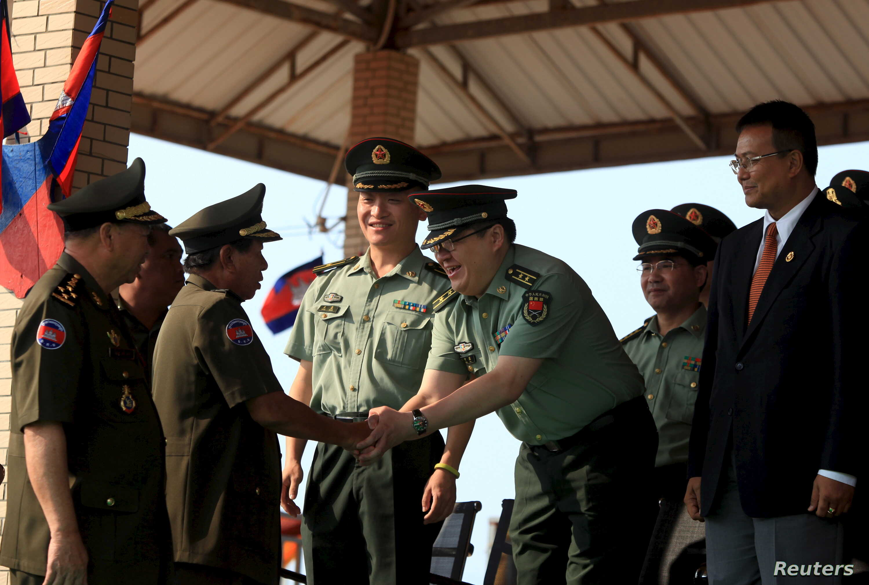 FILE - Cambodian Defense Minister Tea Banh, second left, shakes hands with a Chinese army adviser during a graduation ceremony at the Army Institute in Kampong Speu province, March 12, 2015.
